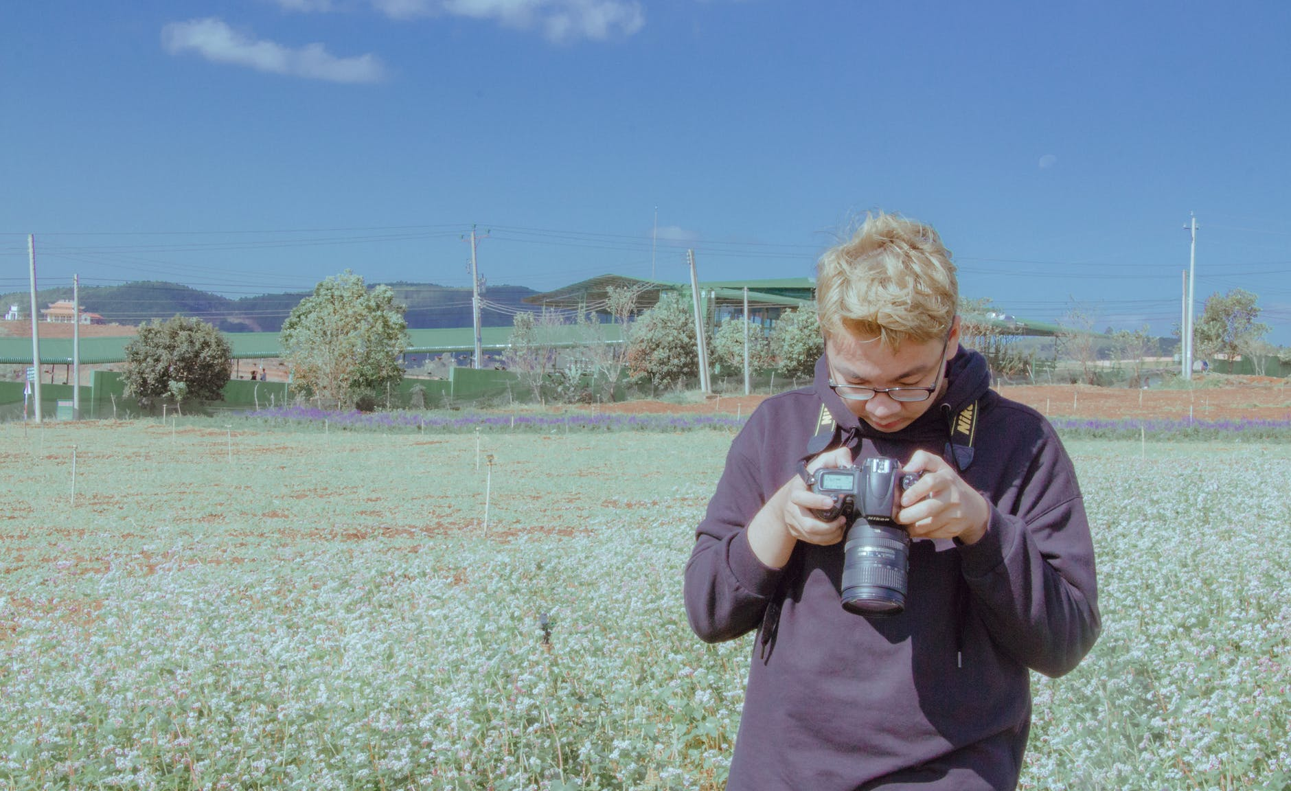Man holding black dslr camera standing on open field under blue sky photo