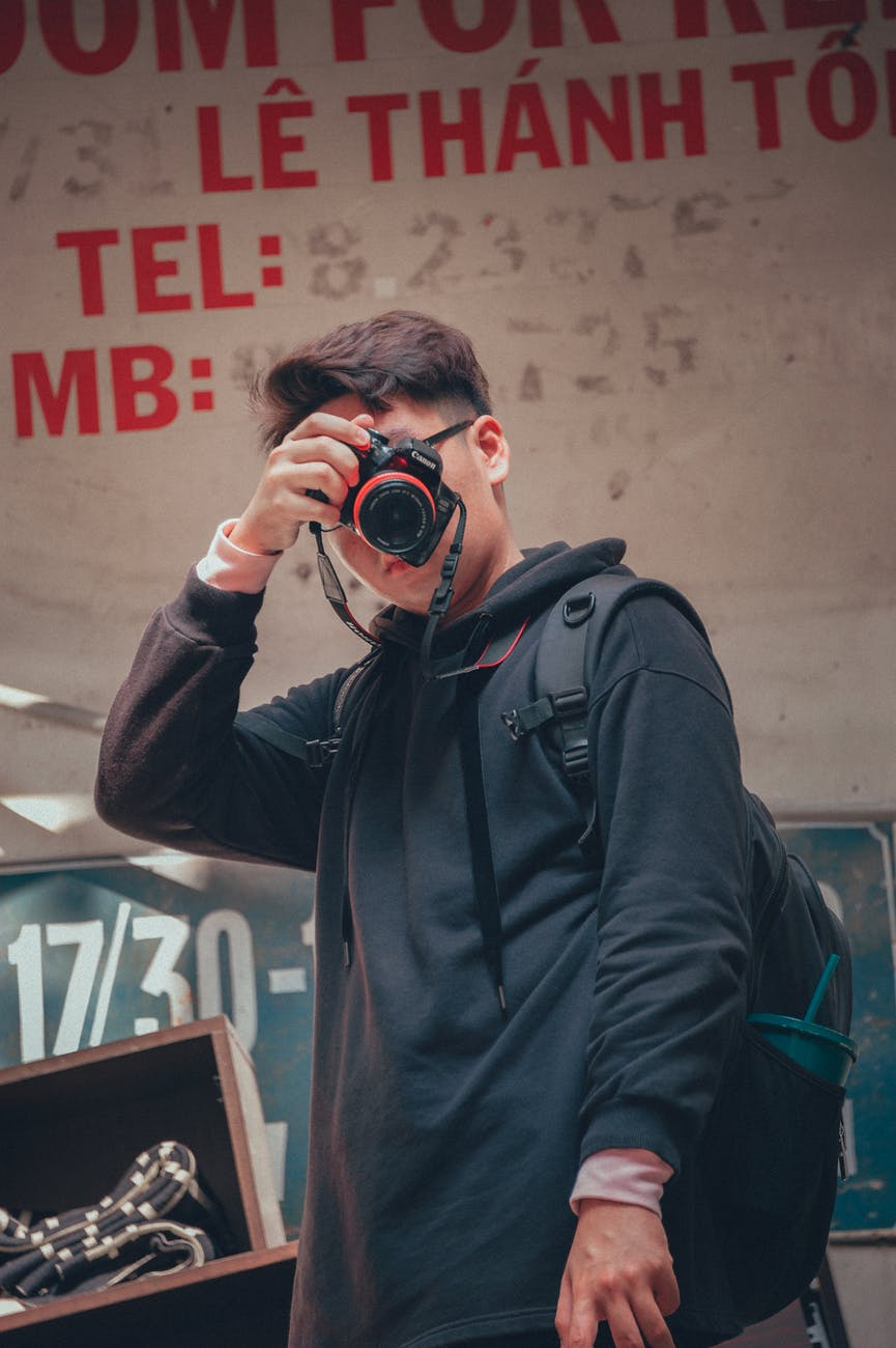 Man holding camera beside text printed wall photo