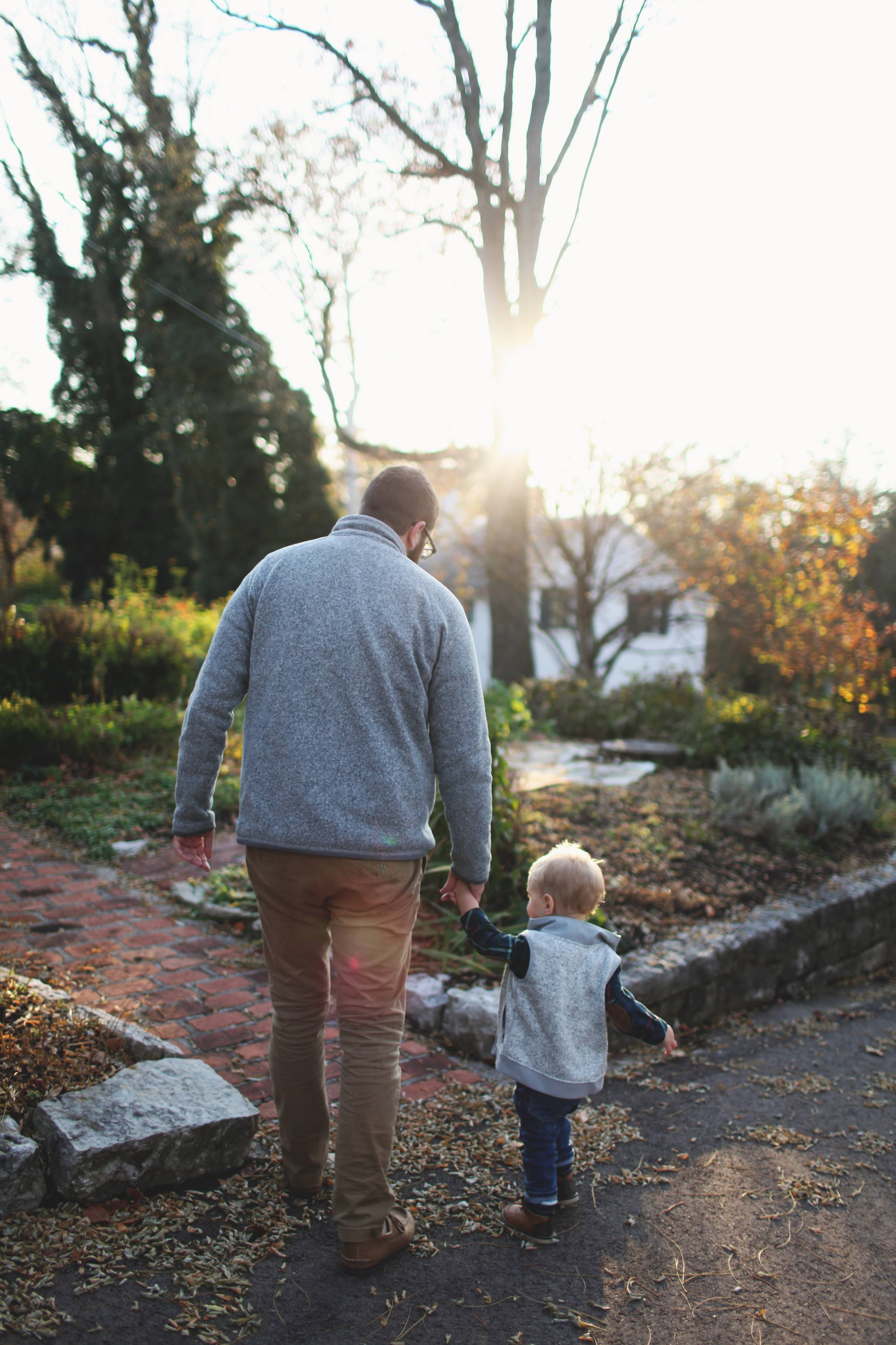 Man holding hands with baby while walking through pathway facing sunlight photo