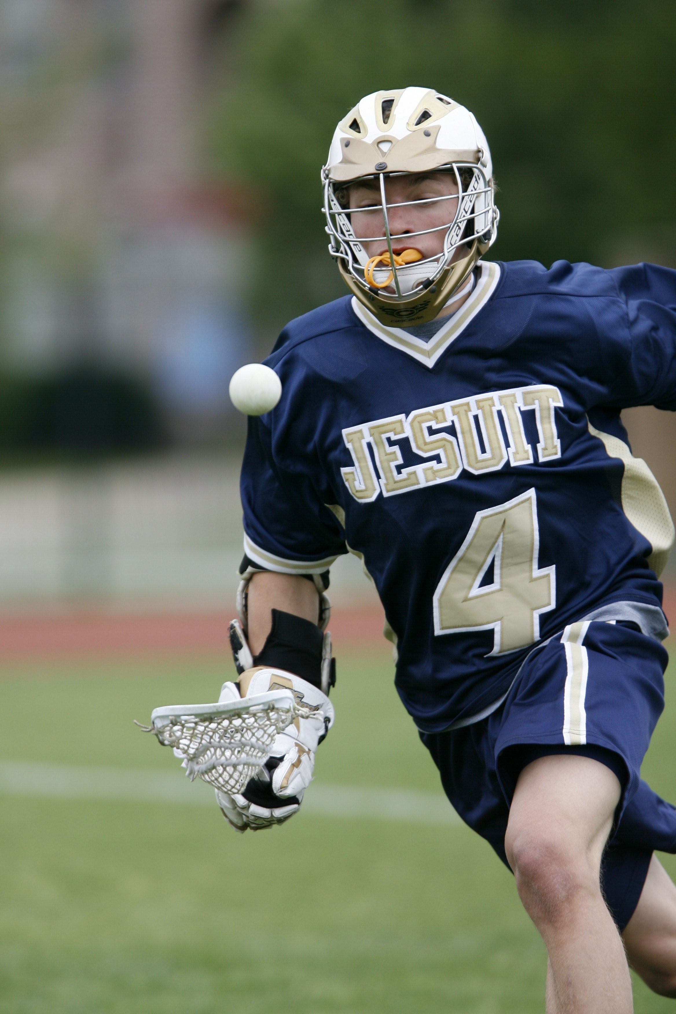 Man holding lacrosse stick running on field during daytime photo