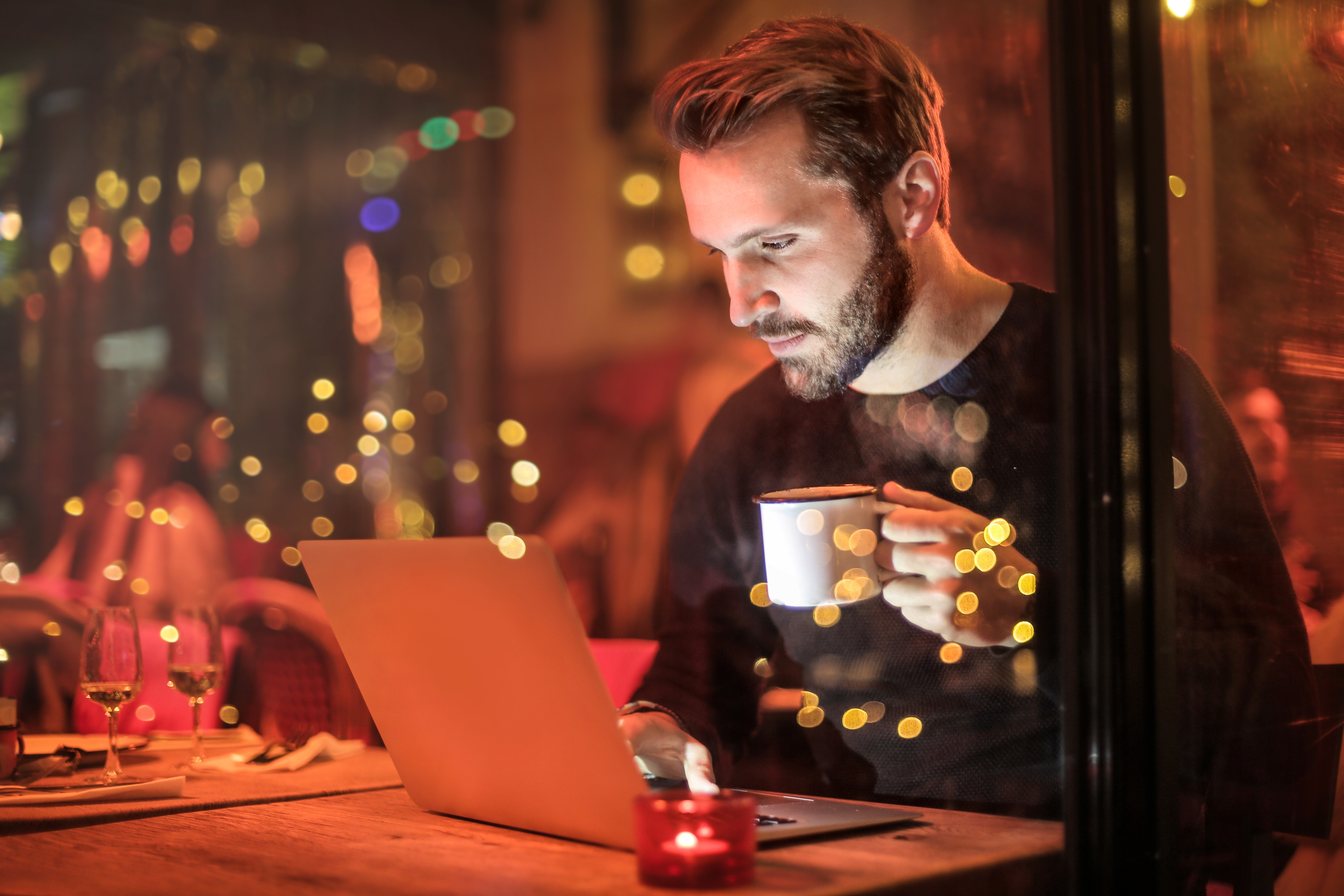 Man holding mug in front of laptop photo