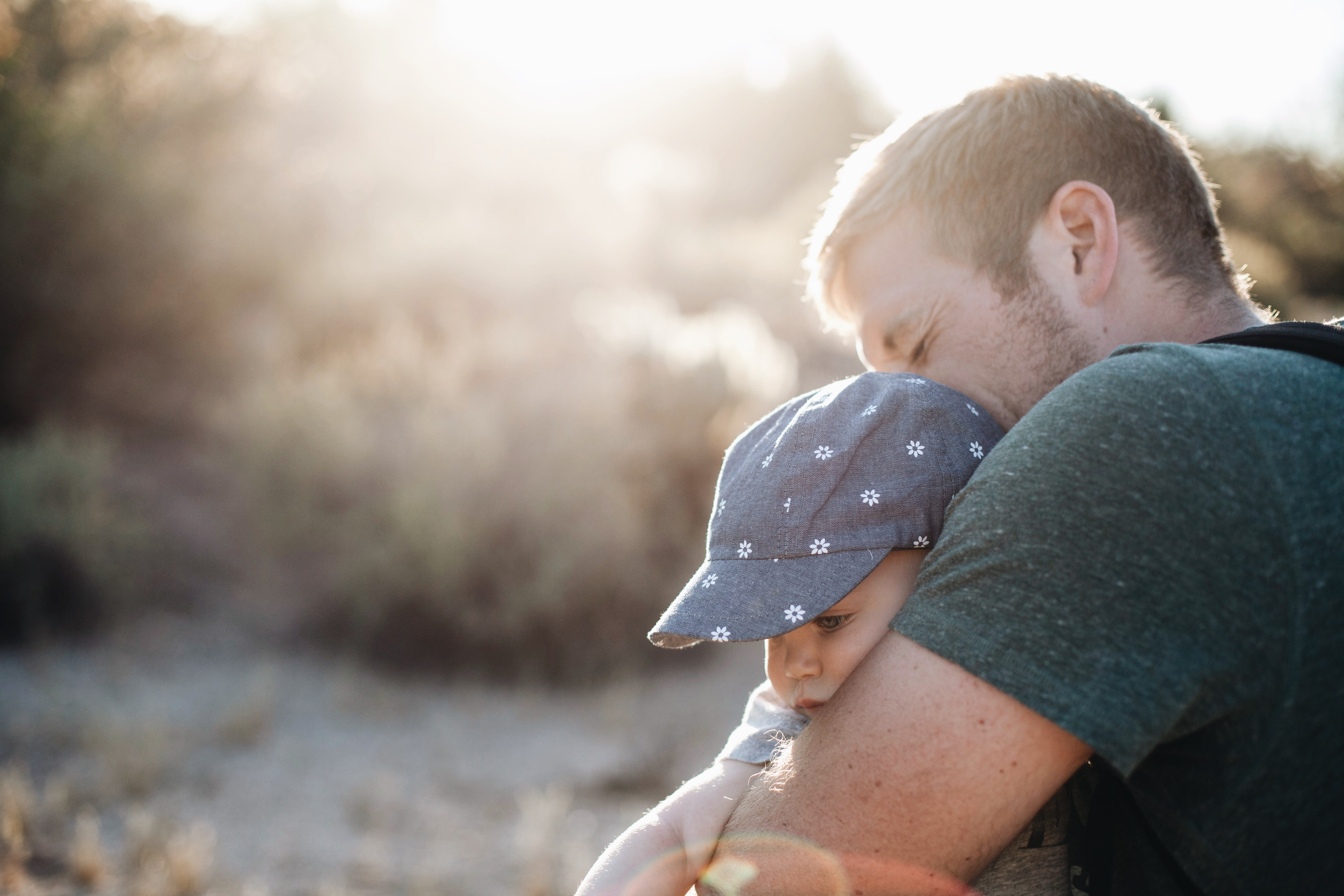 Man hugging the baby in blue floral fitted cap during daytime photo