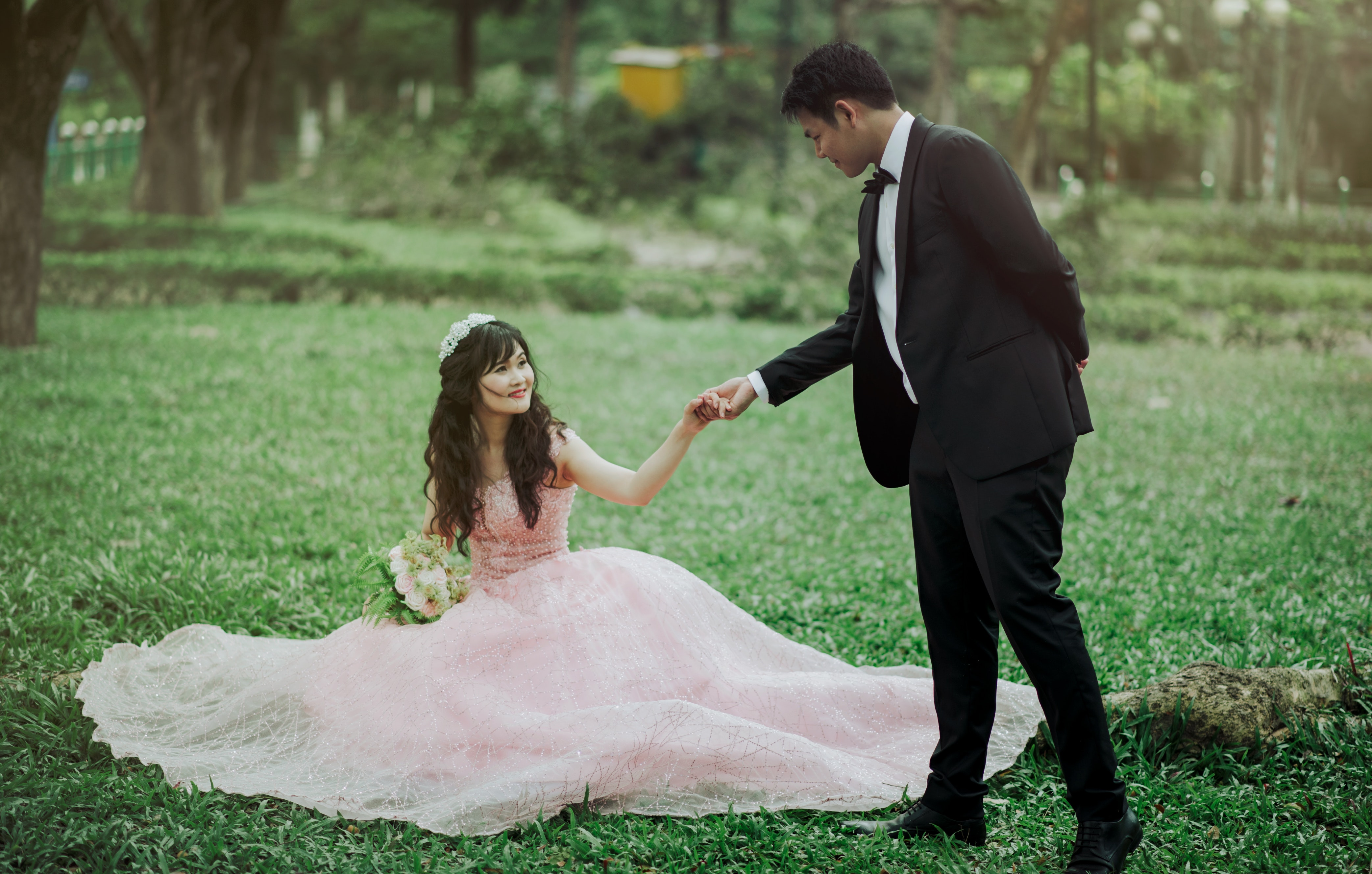 Man in 2-piece suit holding woman in peach-colored wedding gown white holding her flower bouquet photo