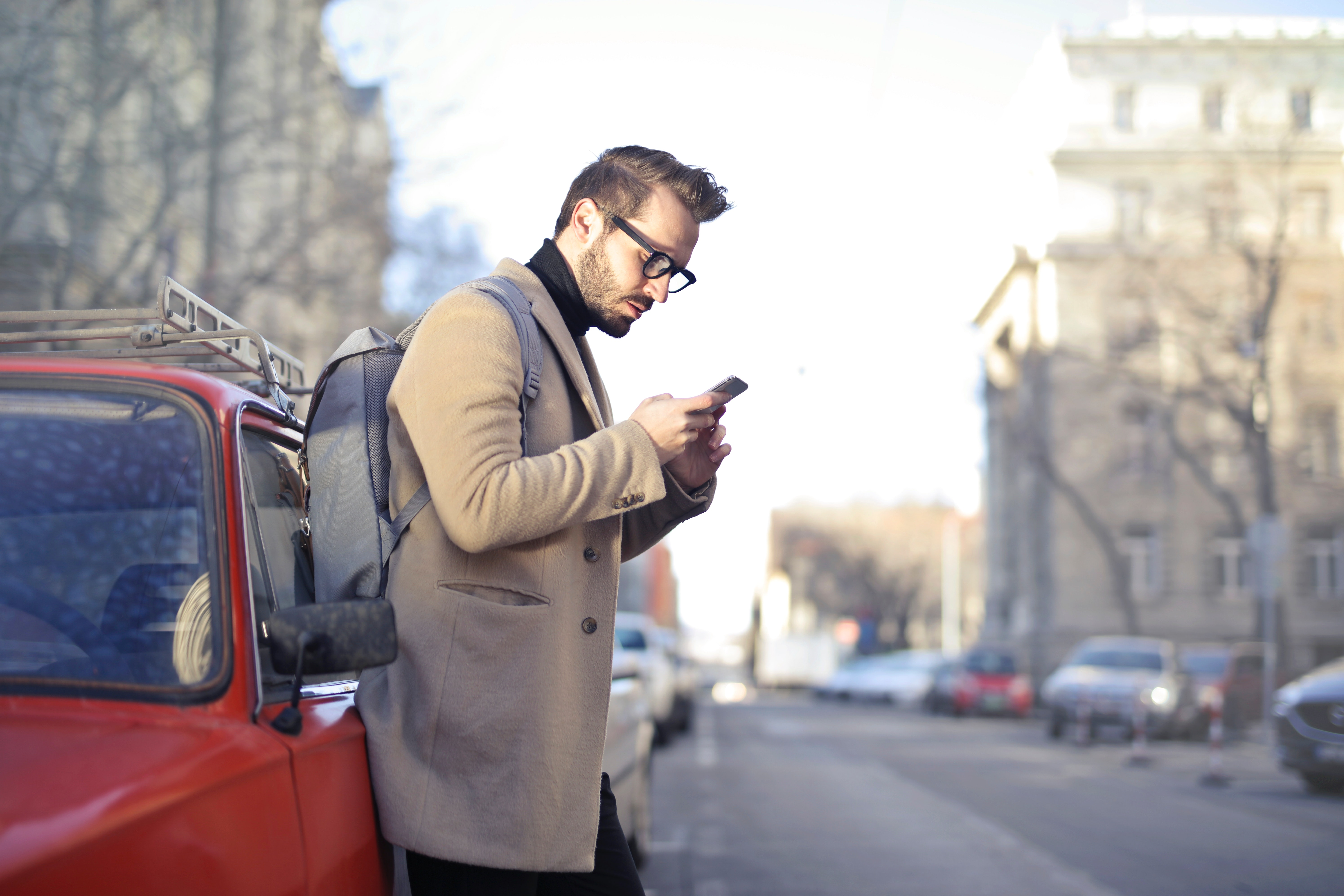 Man in beige coat holding phone leaning on red vehicle photo