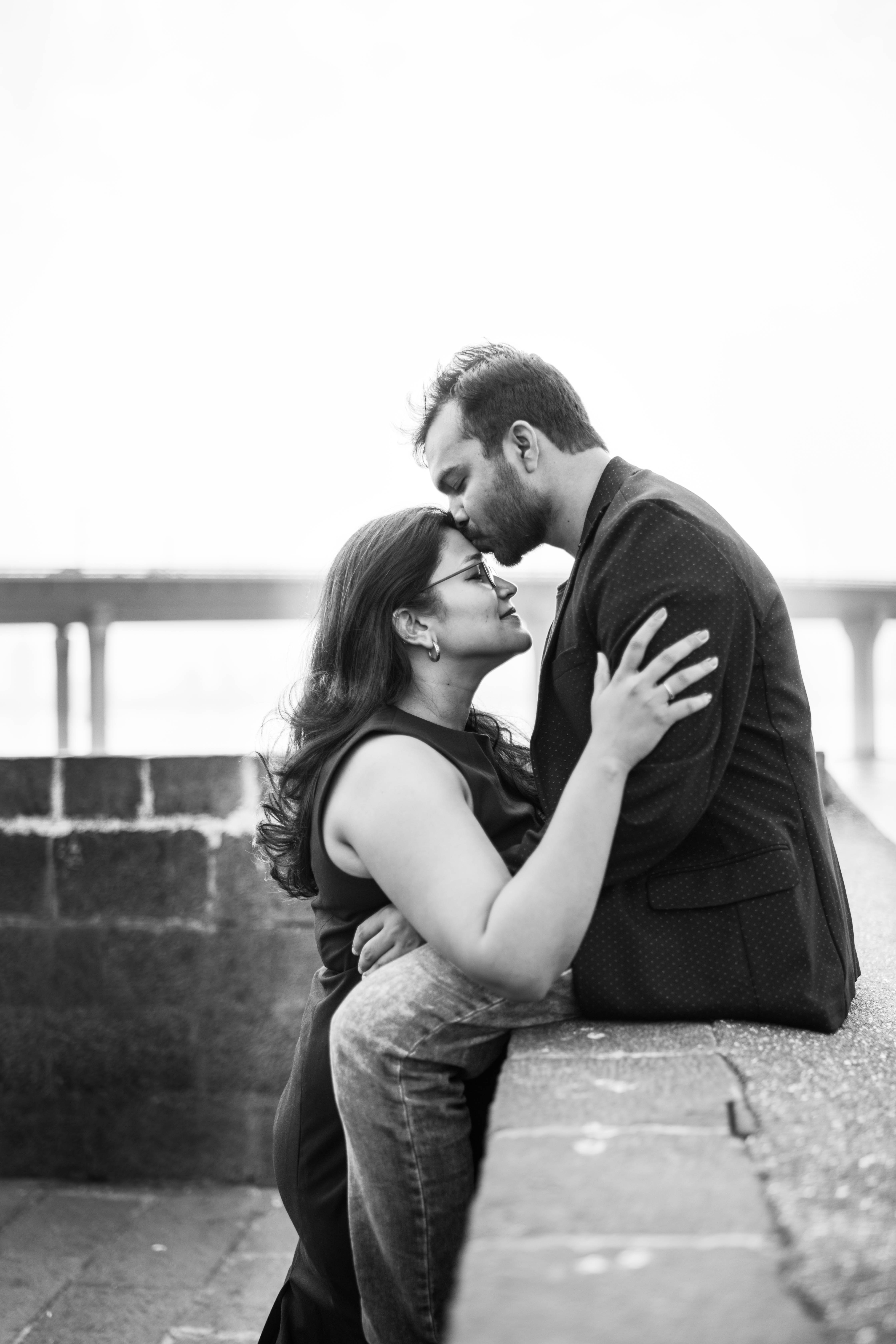 Man in black coat sitting while kissing woman photo