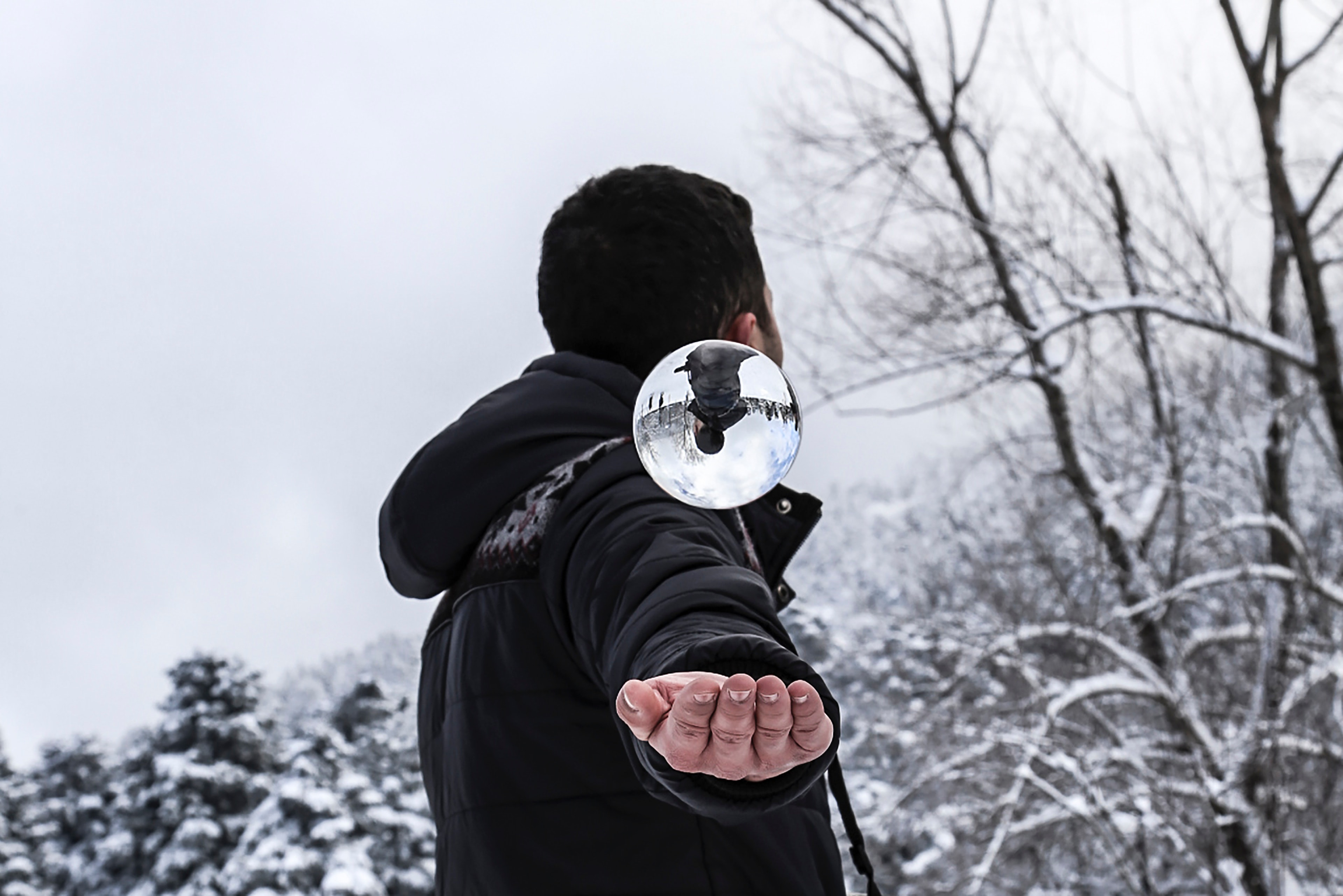 Man in black hoodie during snow weather at daytime photo