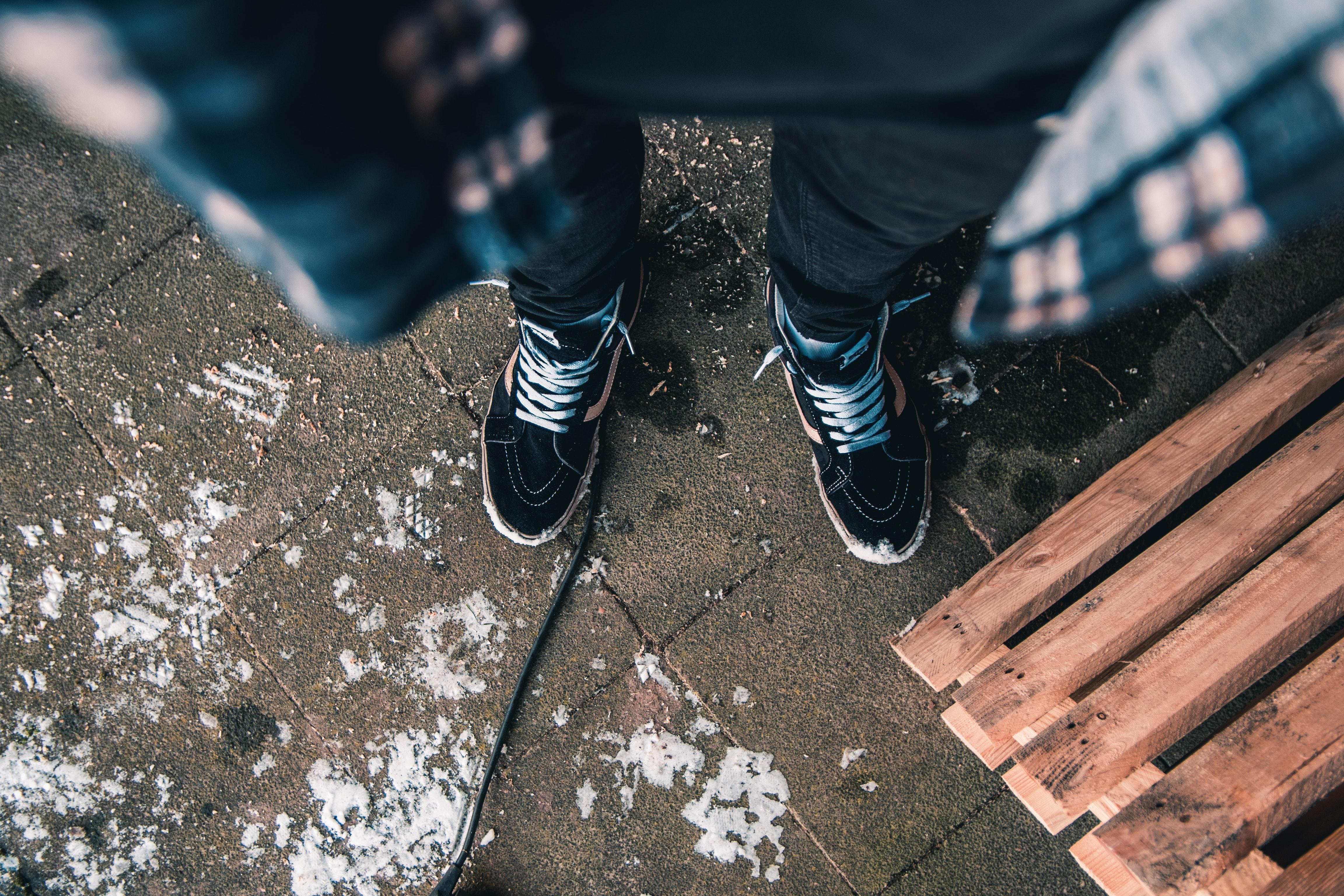 Man in black jeans wearing pair of vans old skool sk8-hi photo