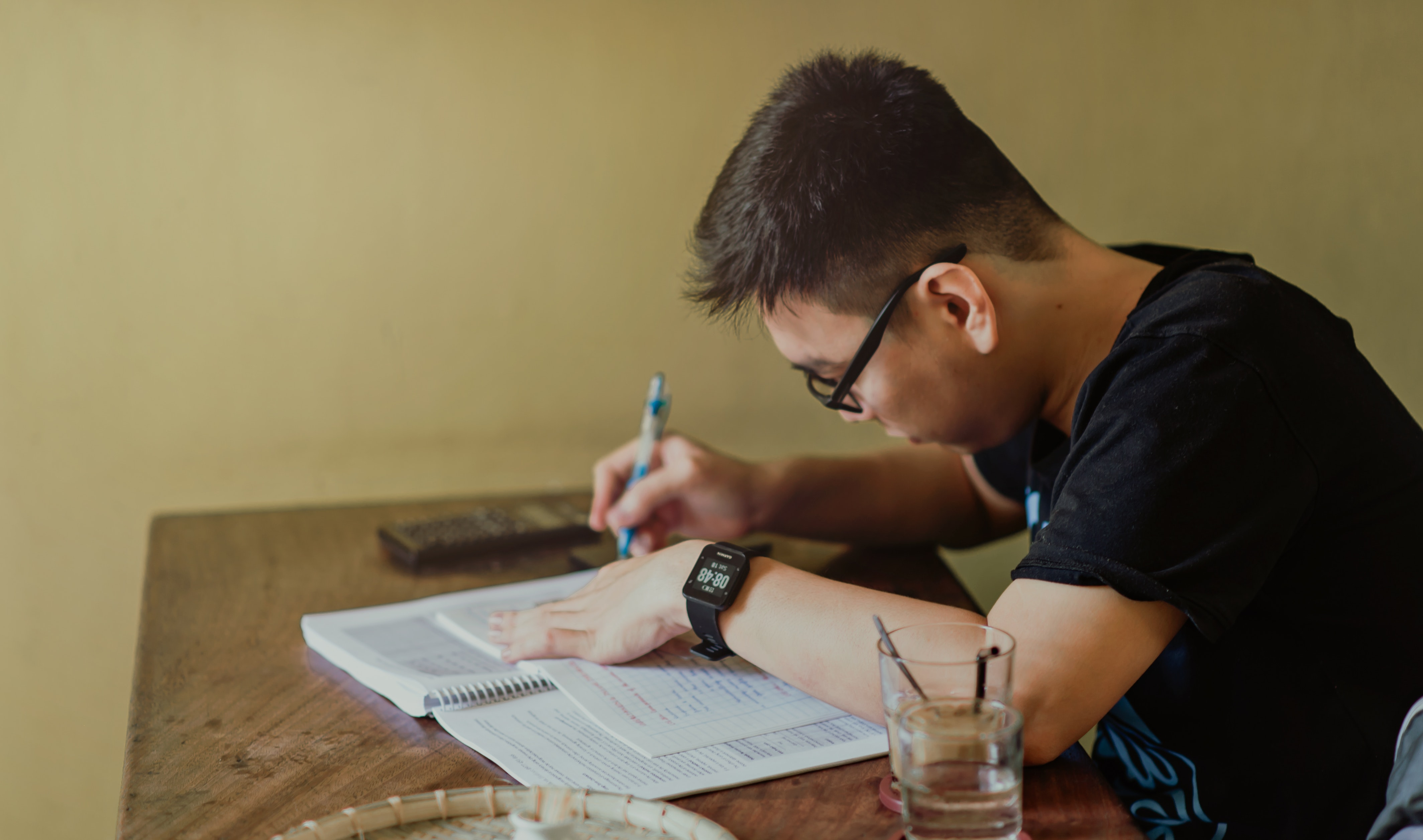 Man in black shirt sitting and writing photo