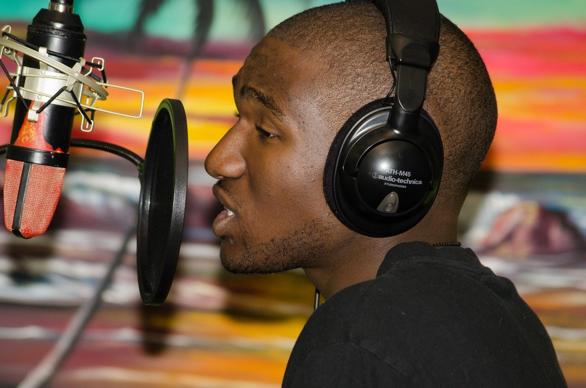Man in black tops wearing black headphones singing in front of black condenser microphone photo