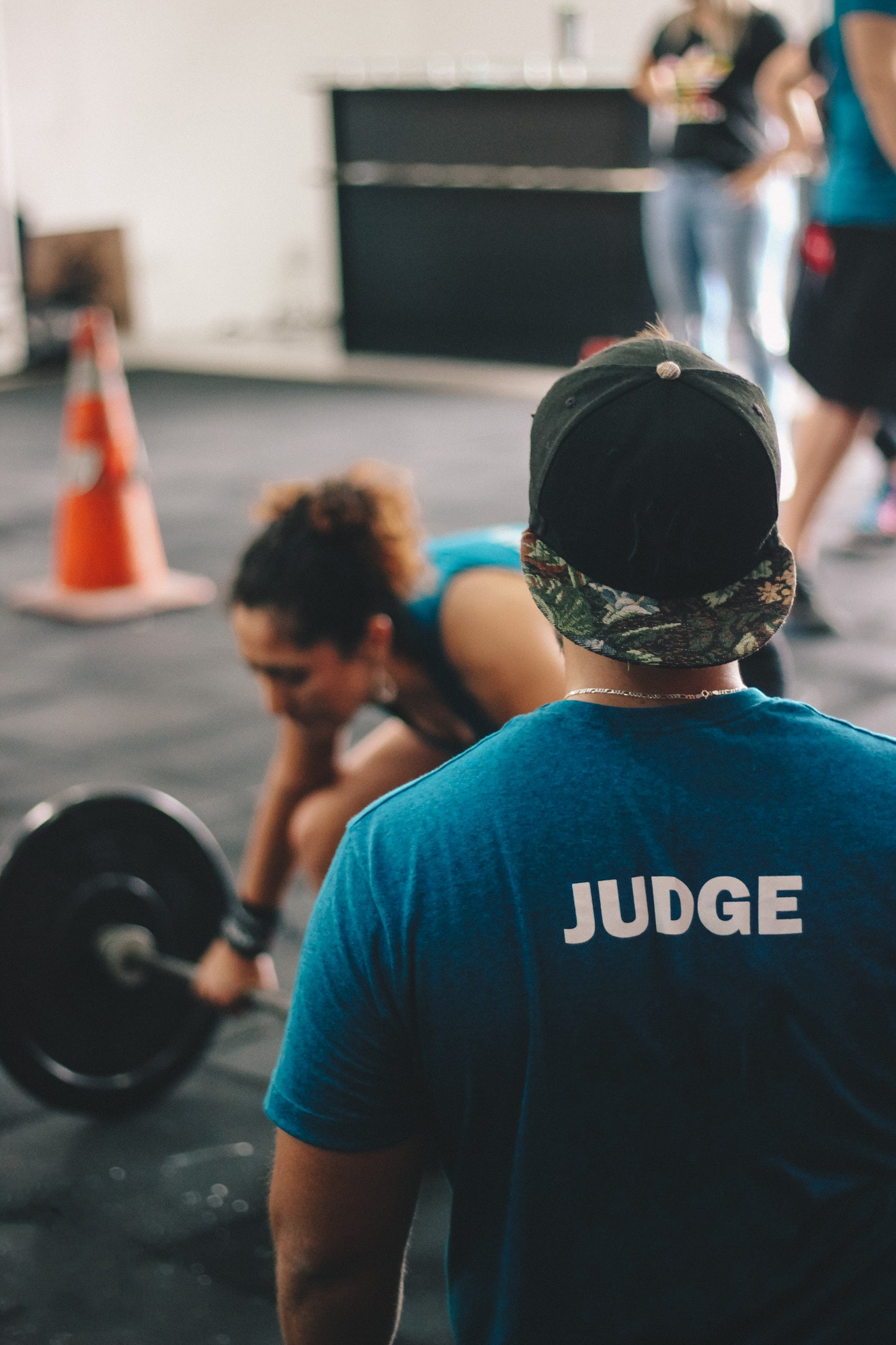 Man in blue crew-neck shirt staring at woman trying to lift barbell photo