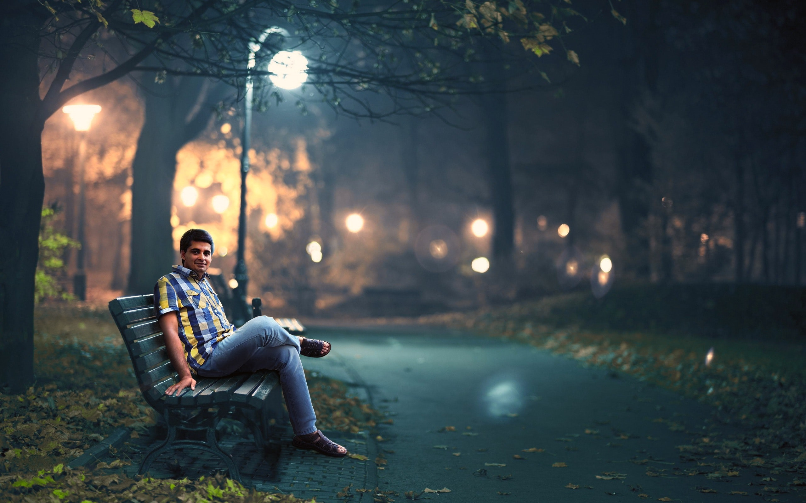 Man in blue denim jeans sitting down by wooden bench near post lamp lighted photo
