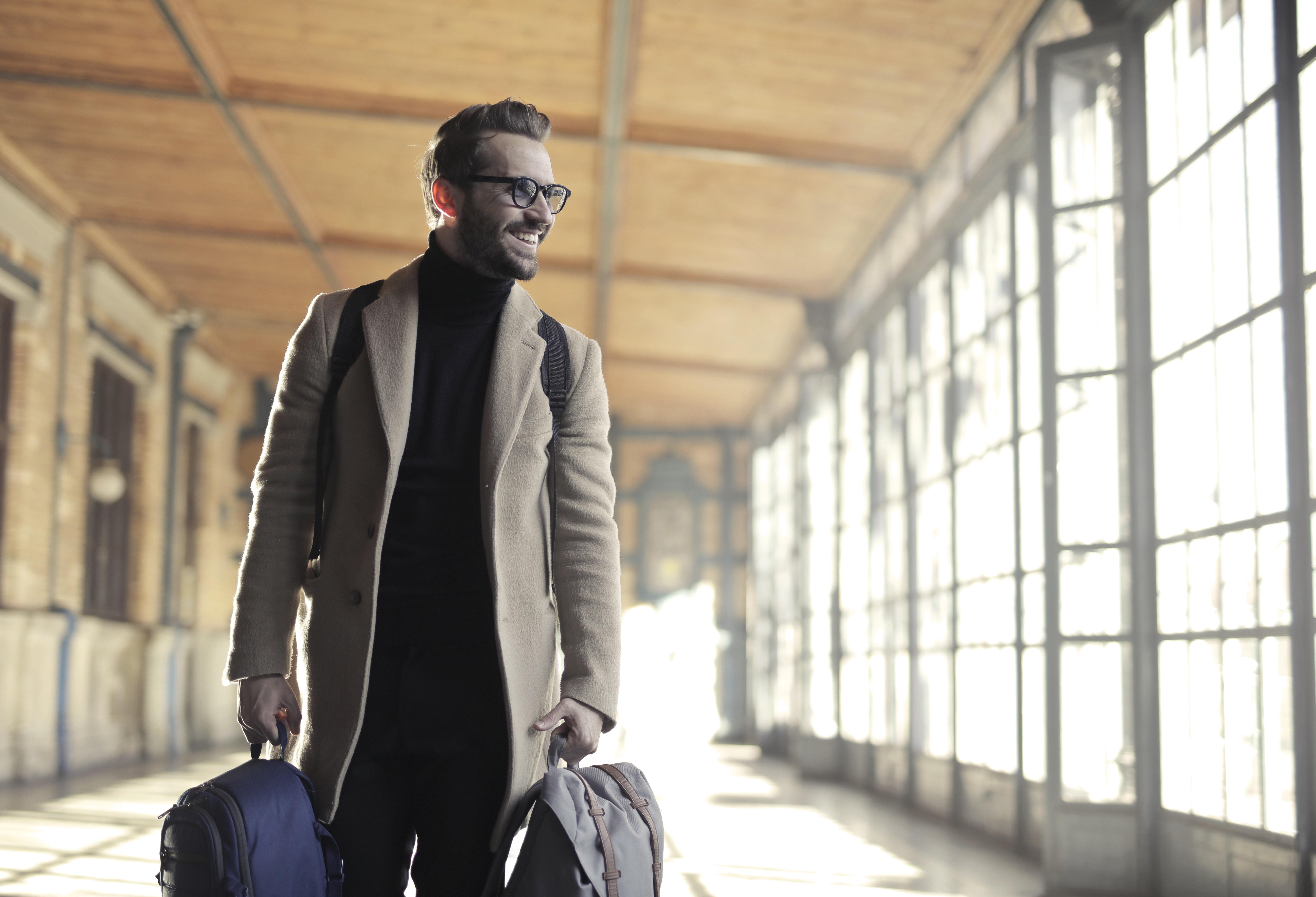 Man in brown robe carrying bag smiling photo