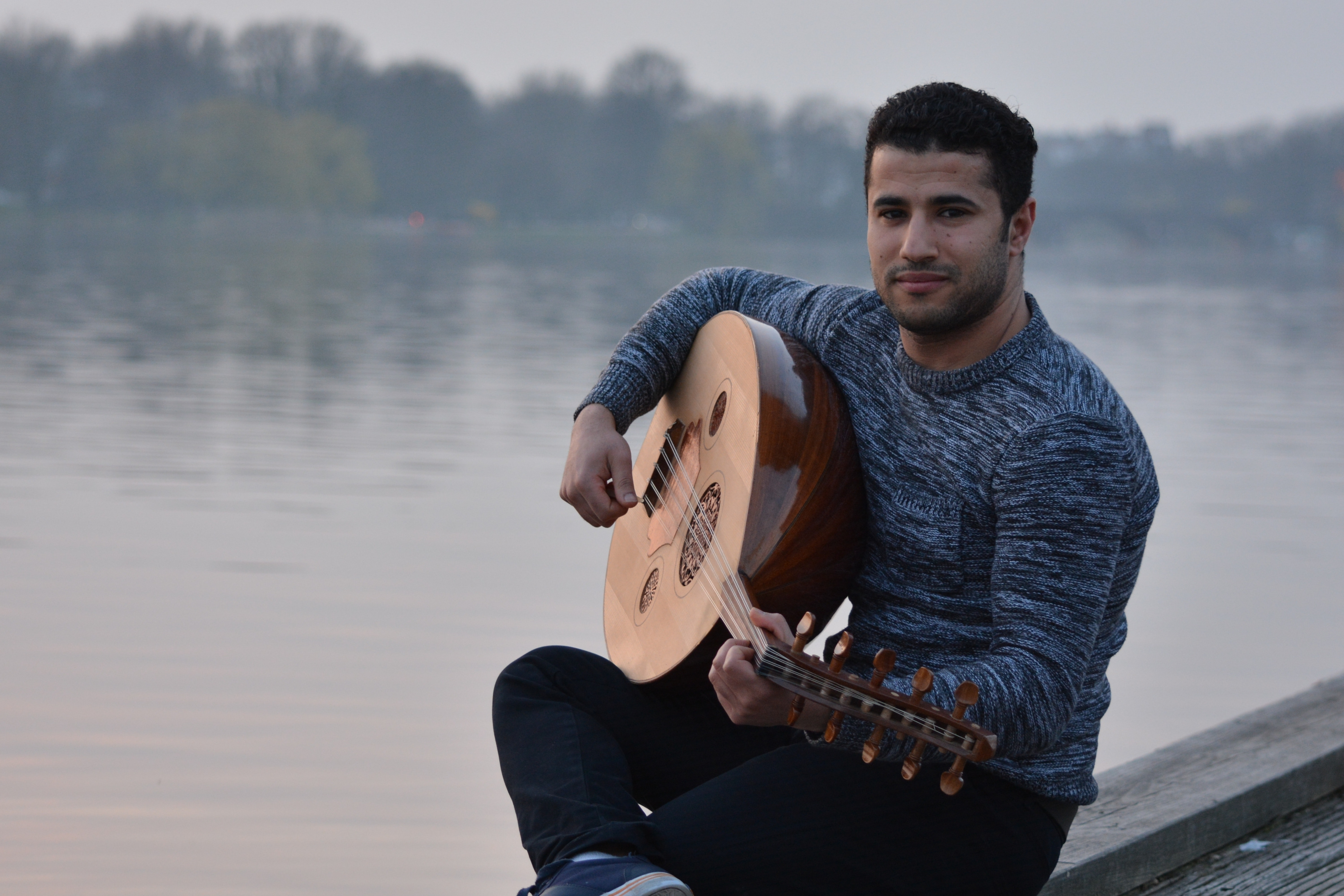 Man in gray crew neck sweatshirt and black pants sitting in gray concrete holding string instrument near body of water photo
