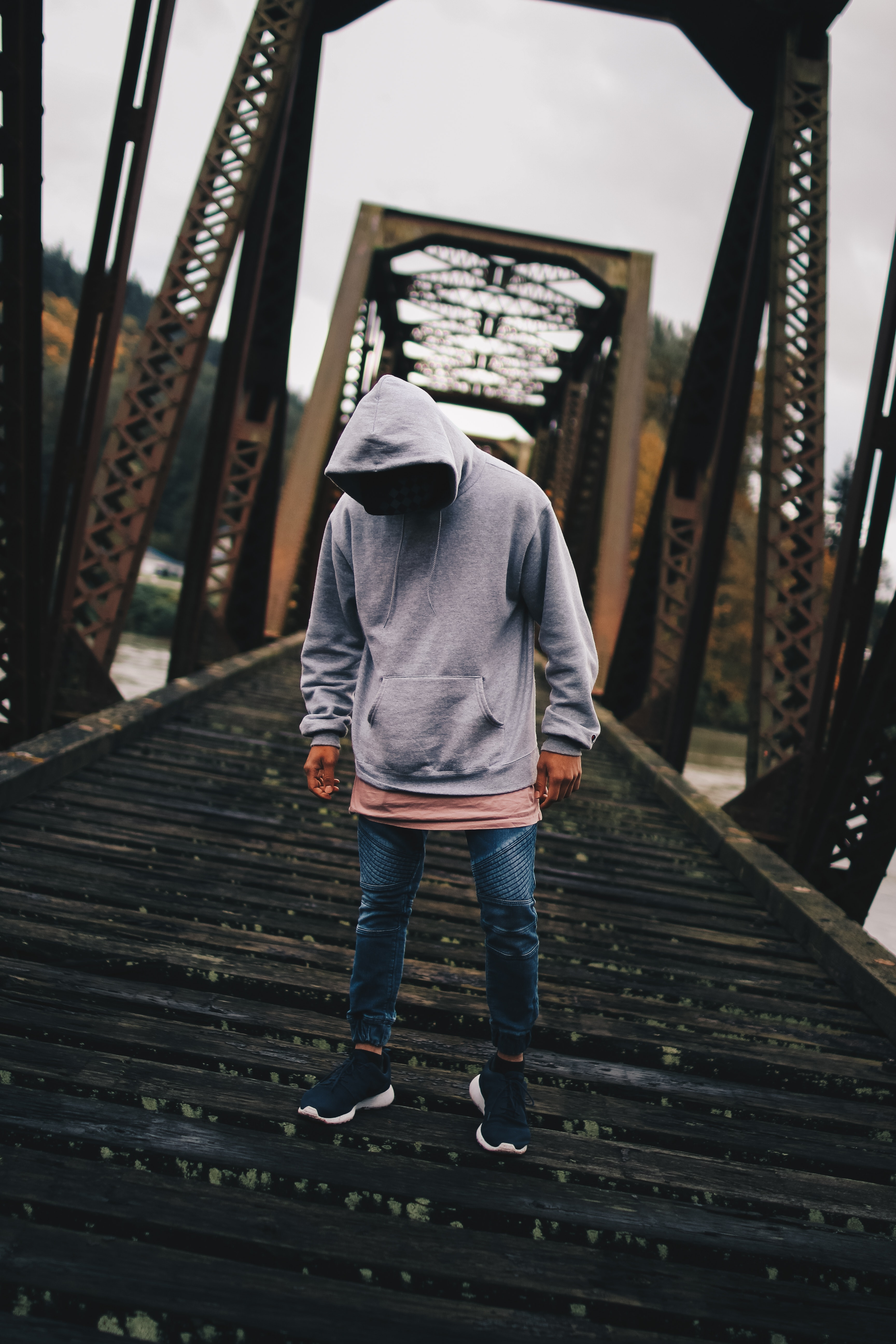 Man in gray pull-over hoodie standing on train rail photo