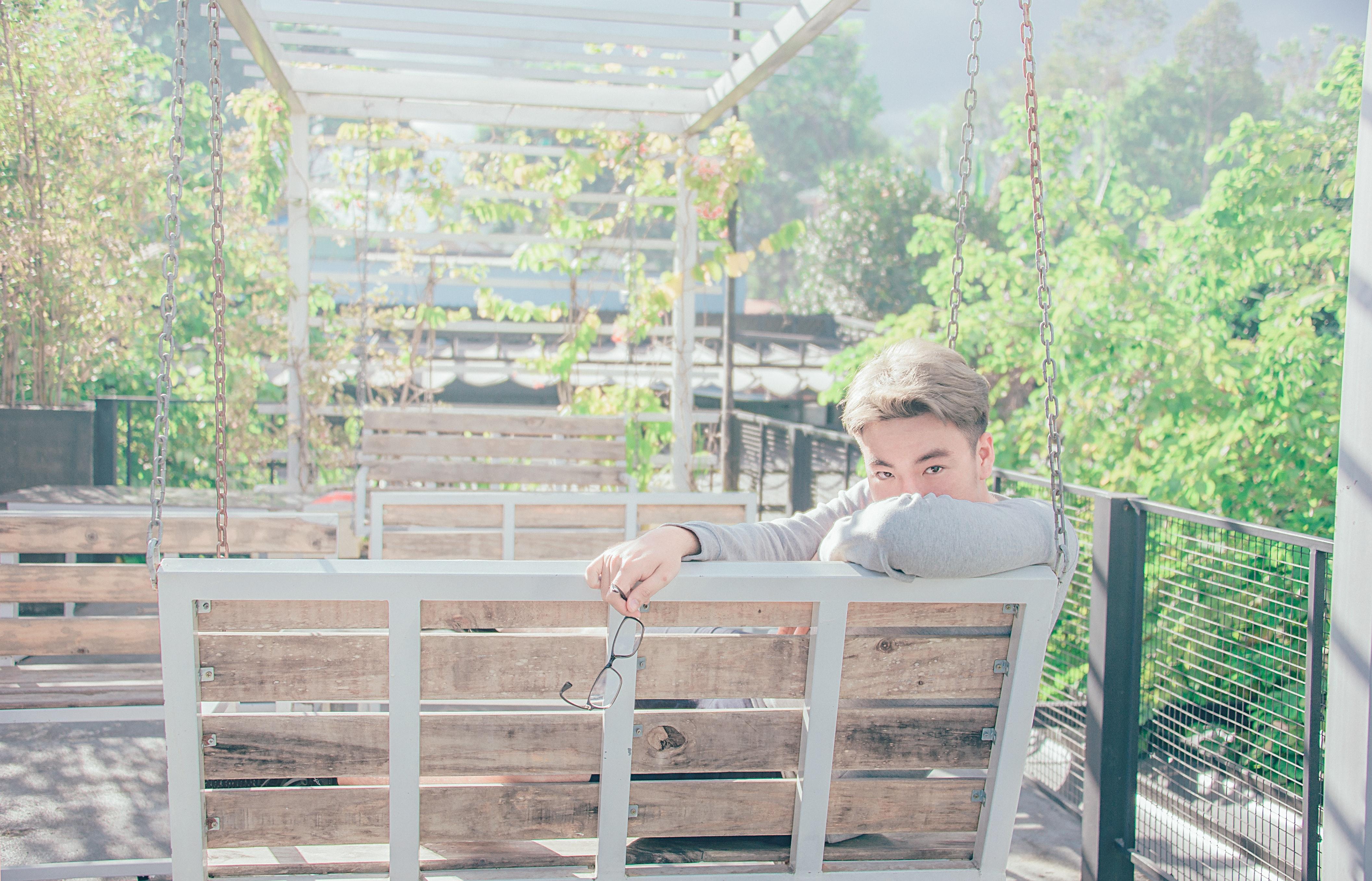 Man in gray shirt sitting on bench photo