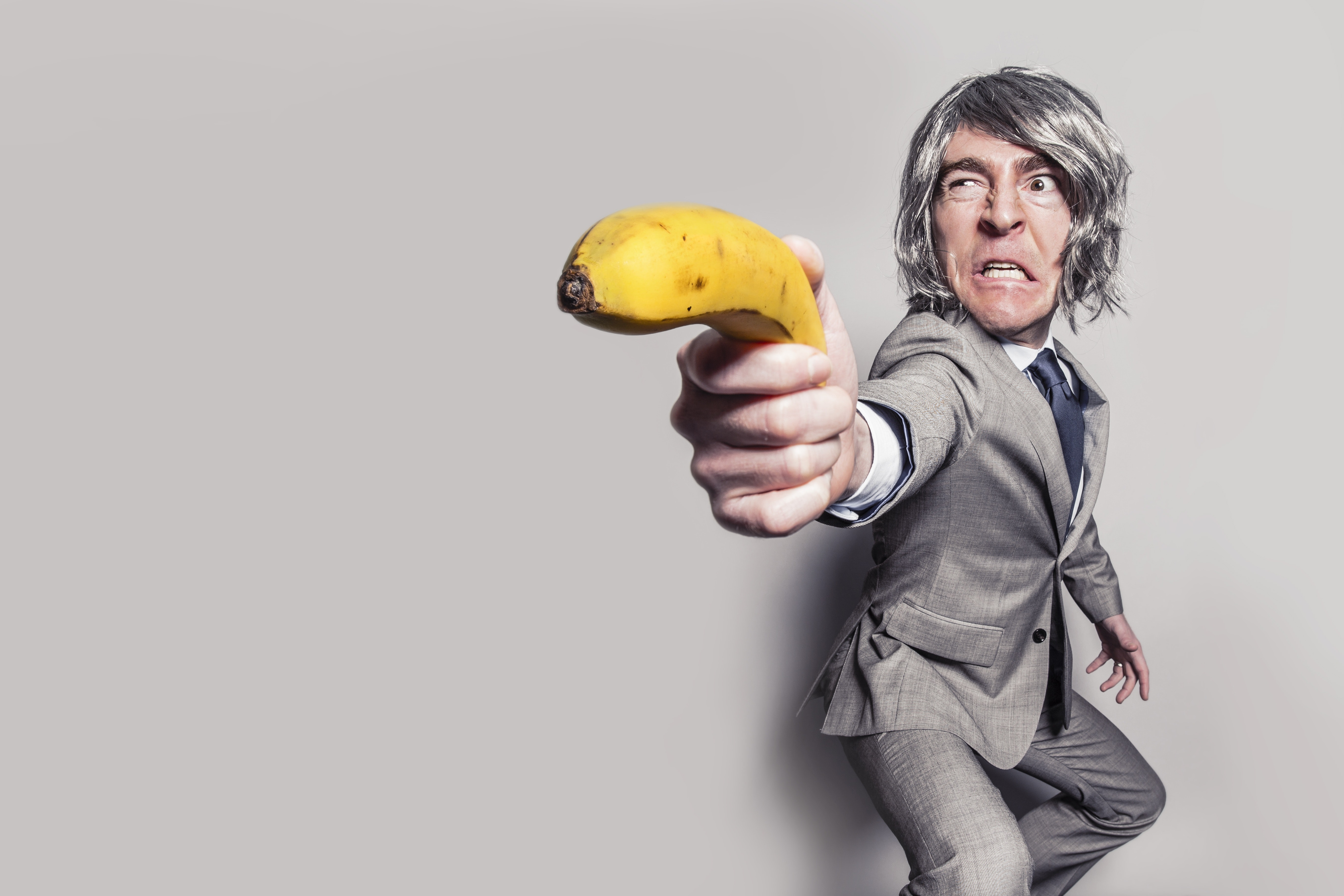 Man in gray suit jacket holding yellow banana fruit while making face photo