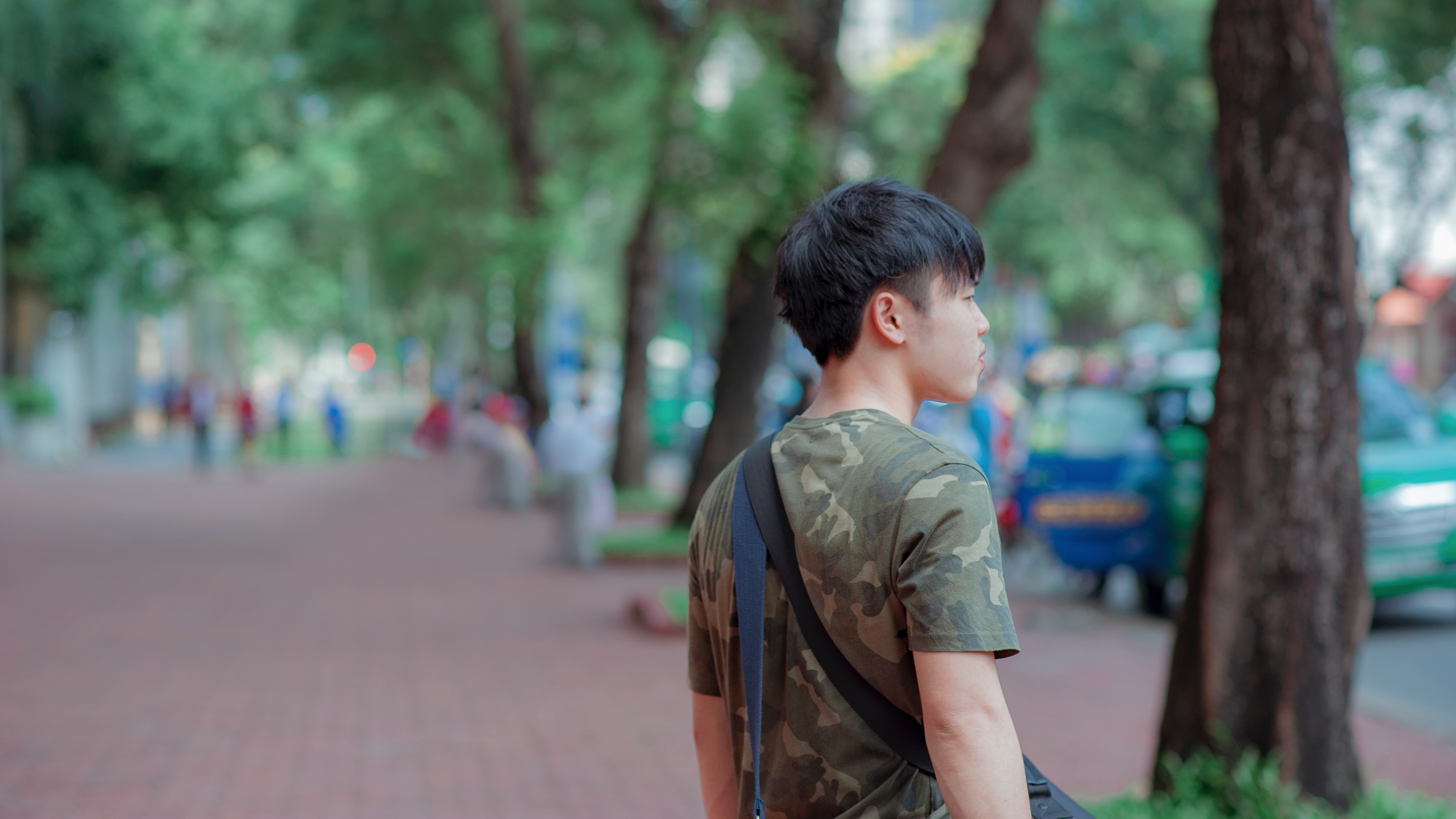Man in green and grey camouflage shirt while standing behind tree photo