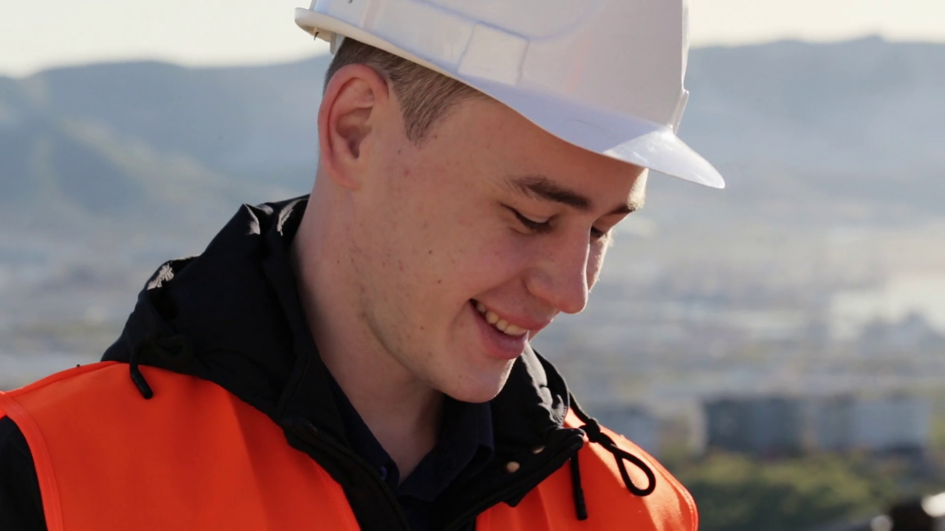 Handsome caucasian man in helmet and vest smiling talking at work ...