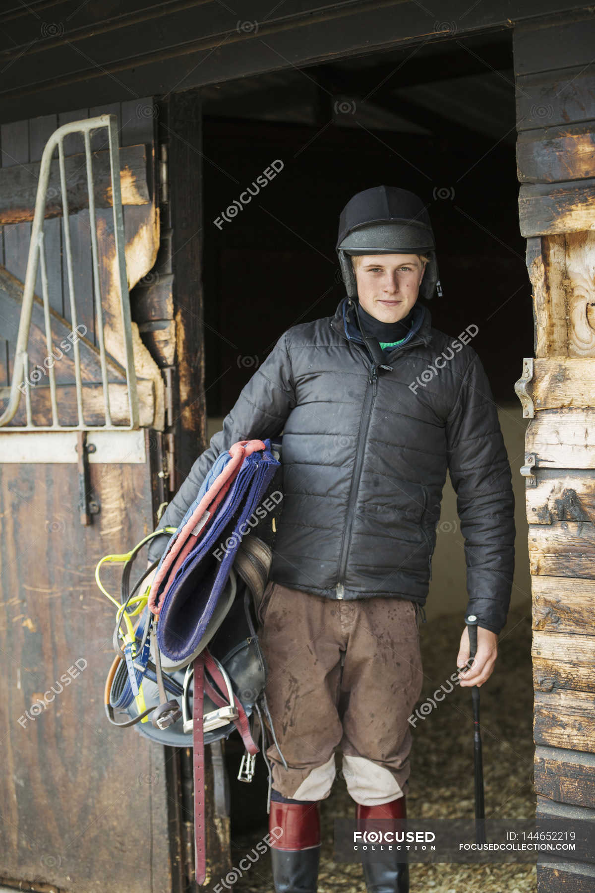 Man in helmet and carrying riding gear — Stock Photo   #144652219