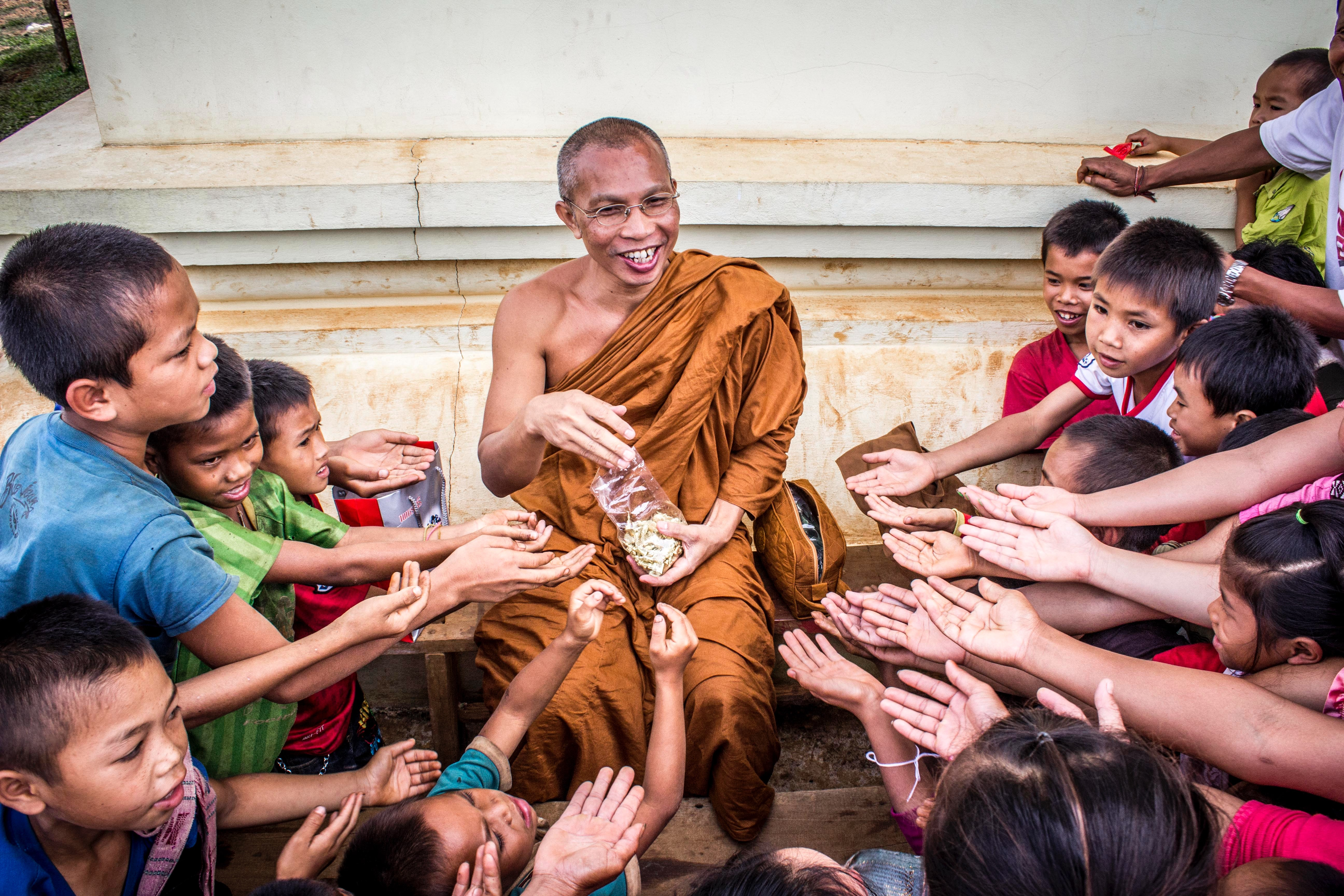 Man in monk dress between group of children photo