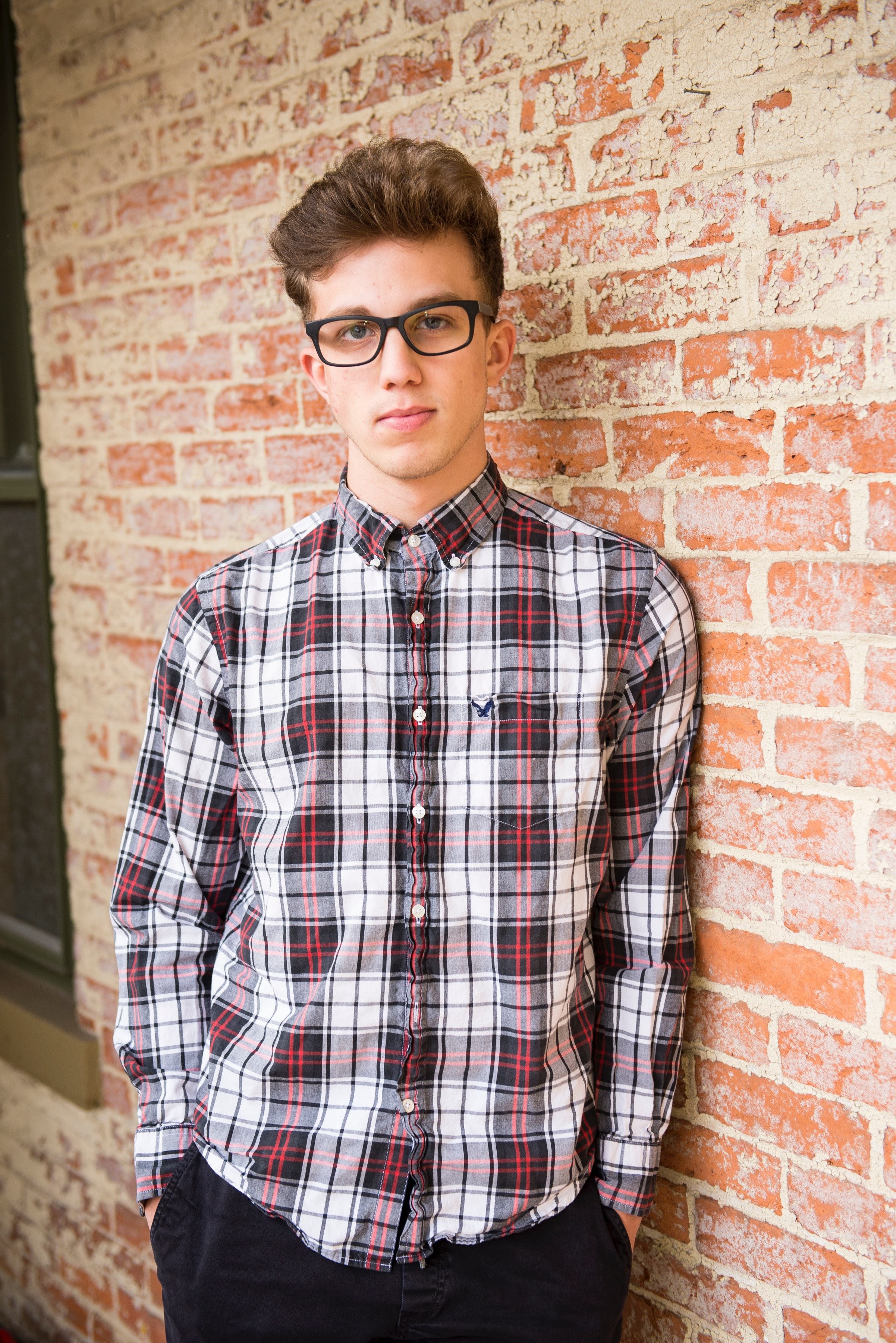 Man in red and white plaid dress shirt and black bottoms with black frame eyeglasses photo