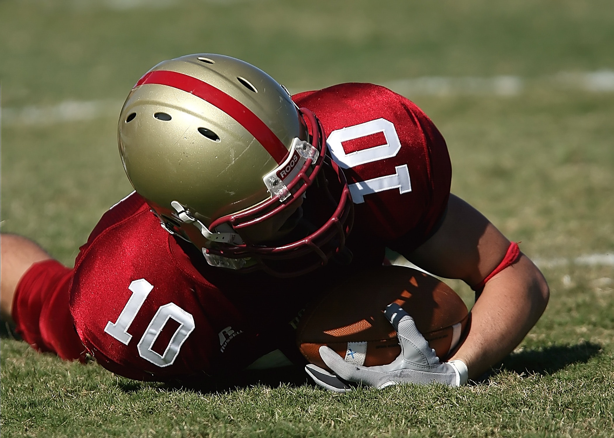 Man in red white football jersey and grey red helmet holding football and lying on green grass field photo