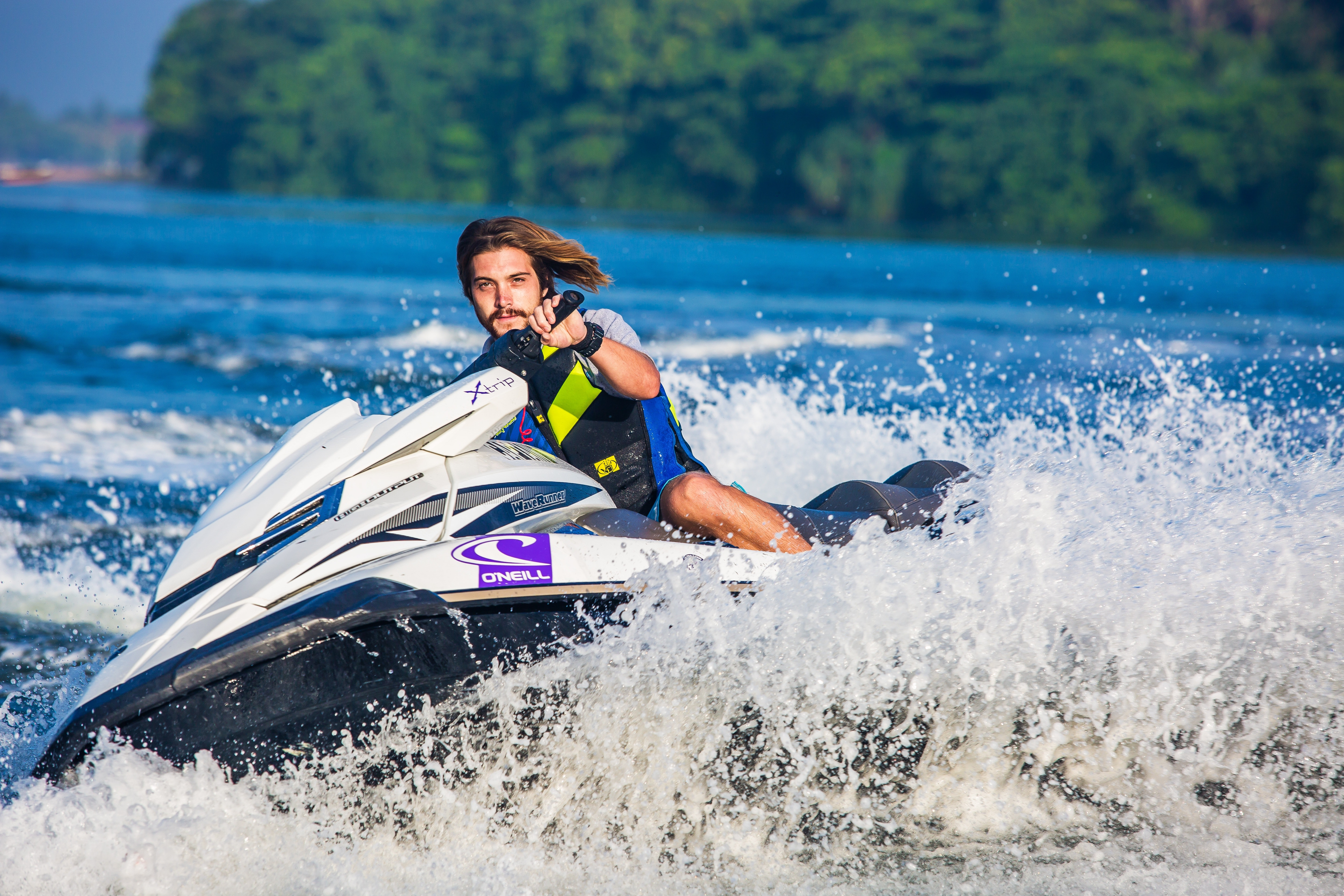 Man in safety vest riding a personal watercraft during daytime photo
