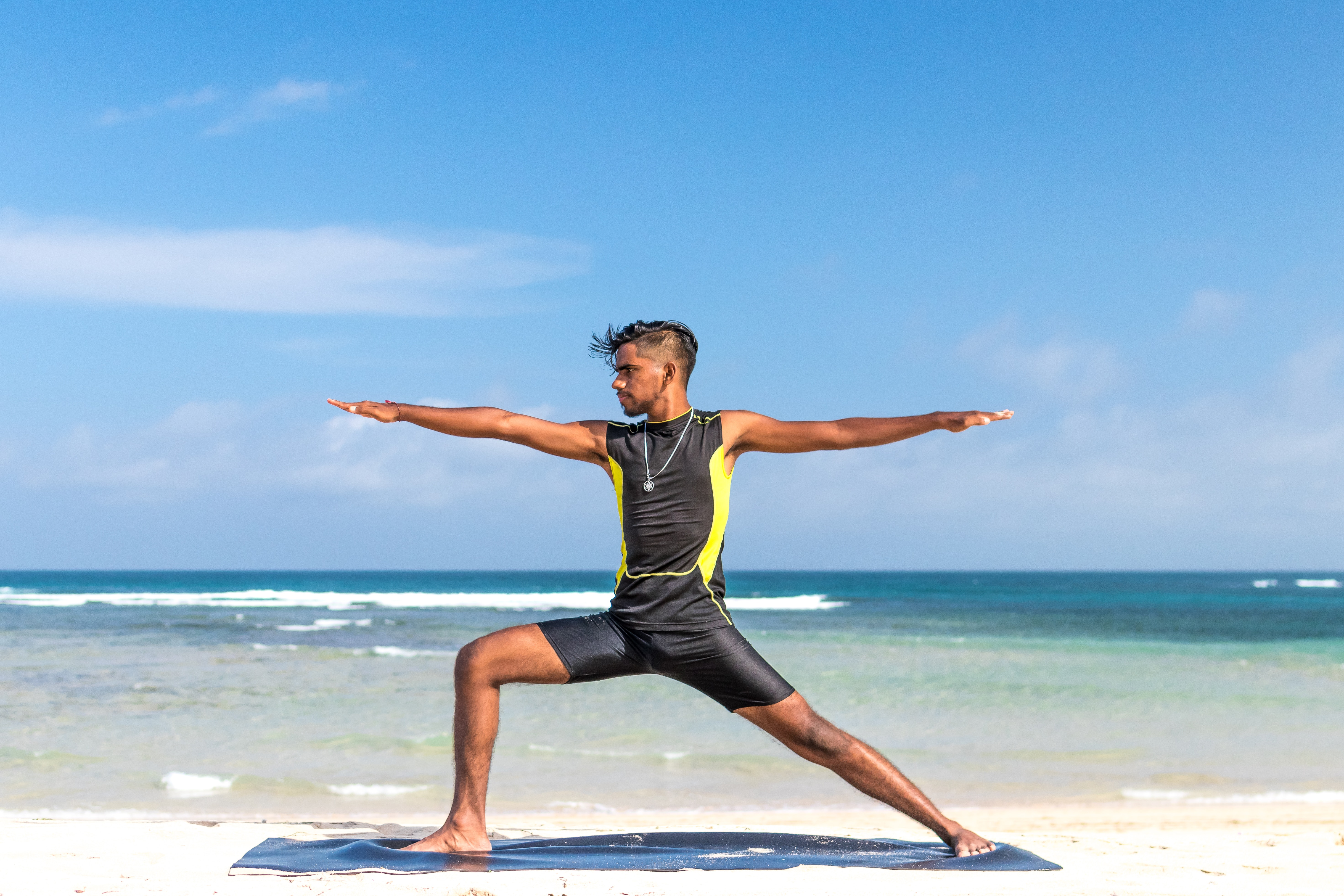 Man in sleeveless wet suit doing some aerobics at the beach photo