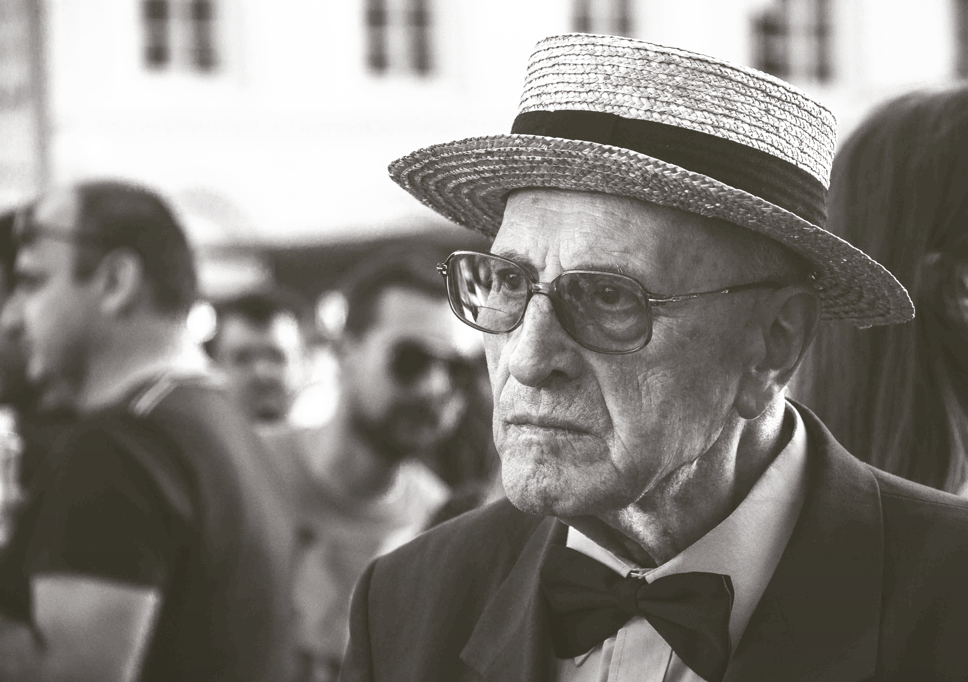 Man in straw hat wearing bow tie with people photo