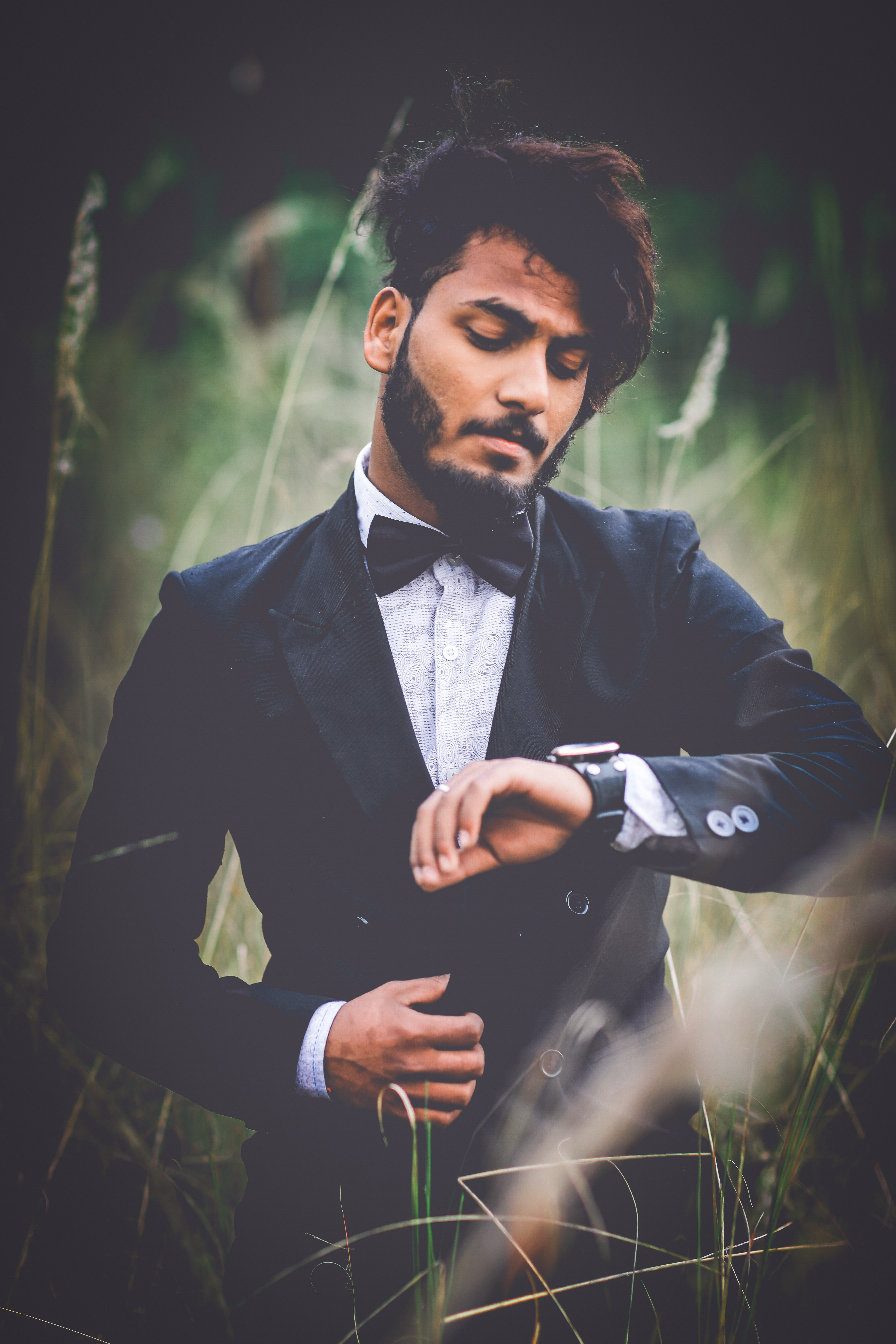 Man in tuxedo suit surrounded by grass photo