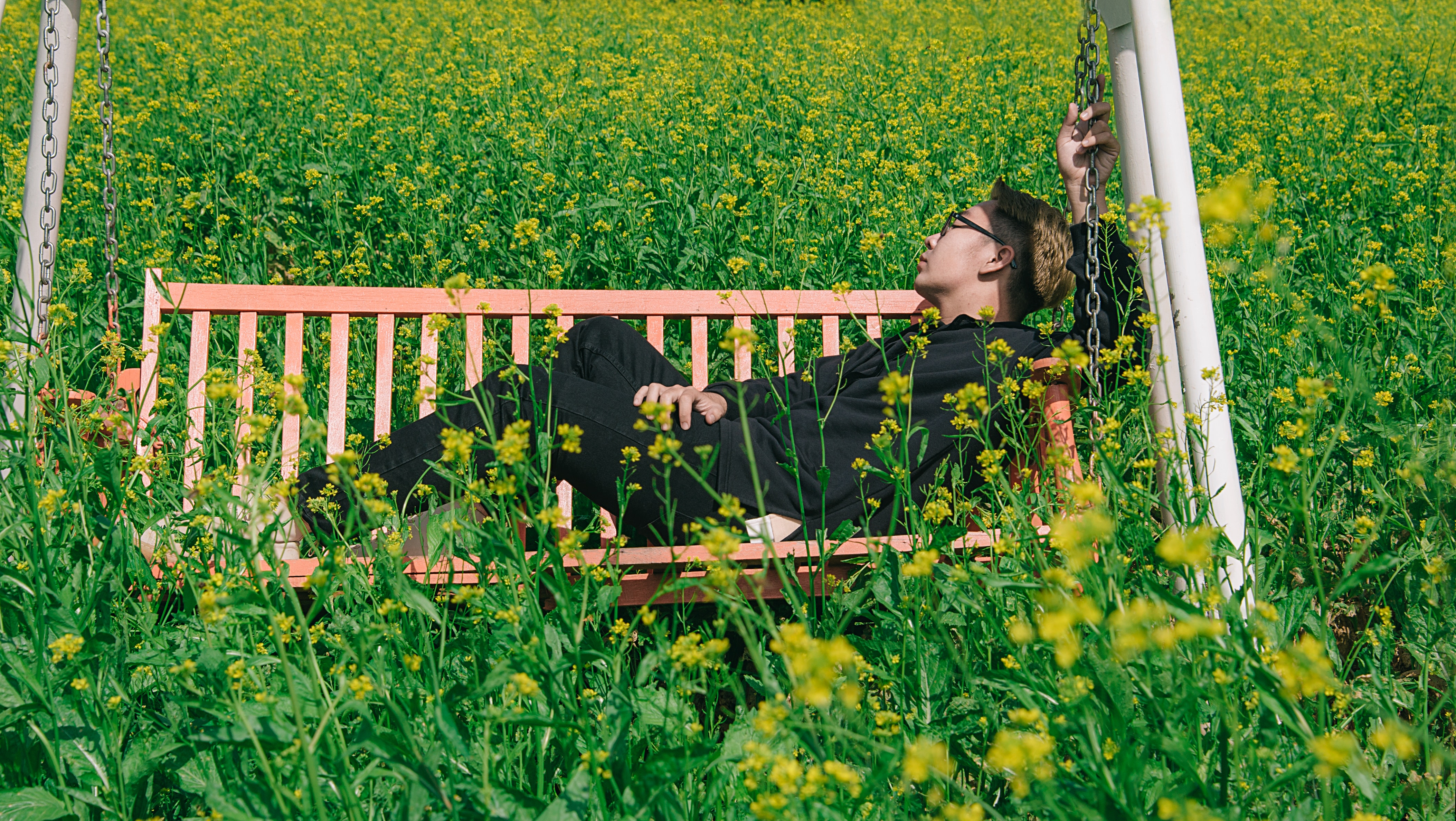 Man in white and brown canopy swing surrounded with yellow petal flower photo