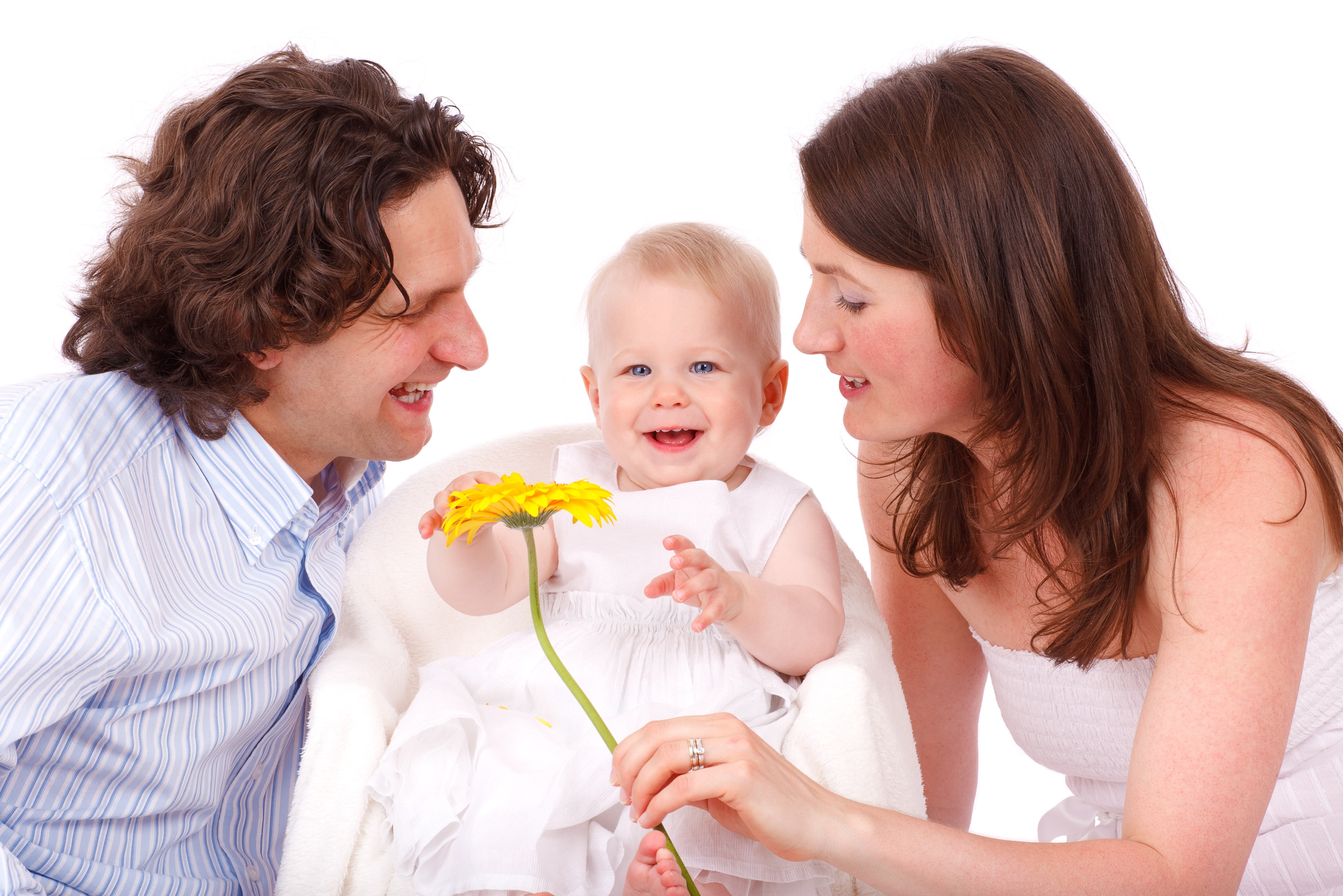 Man in white and gray stripe button up long sleeve shirt facing baby in white sleeveless dress beside woman in white strapless dress holding yellow flower photo