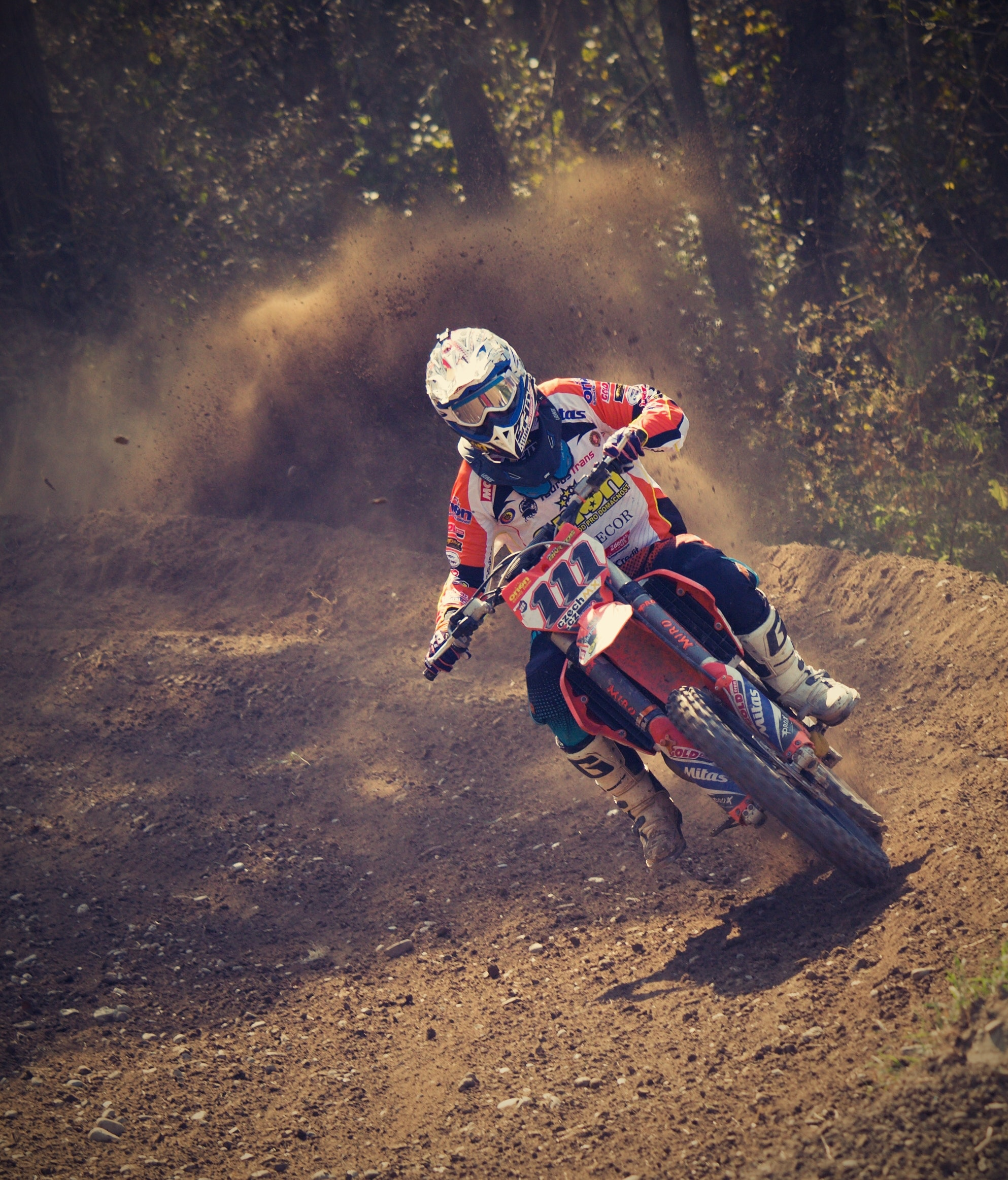 Man in white and orange motocross overall riding his motocross dirt bike during daytime photo
