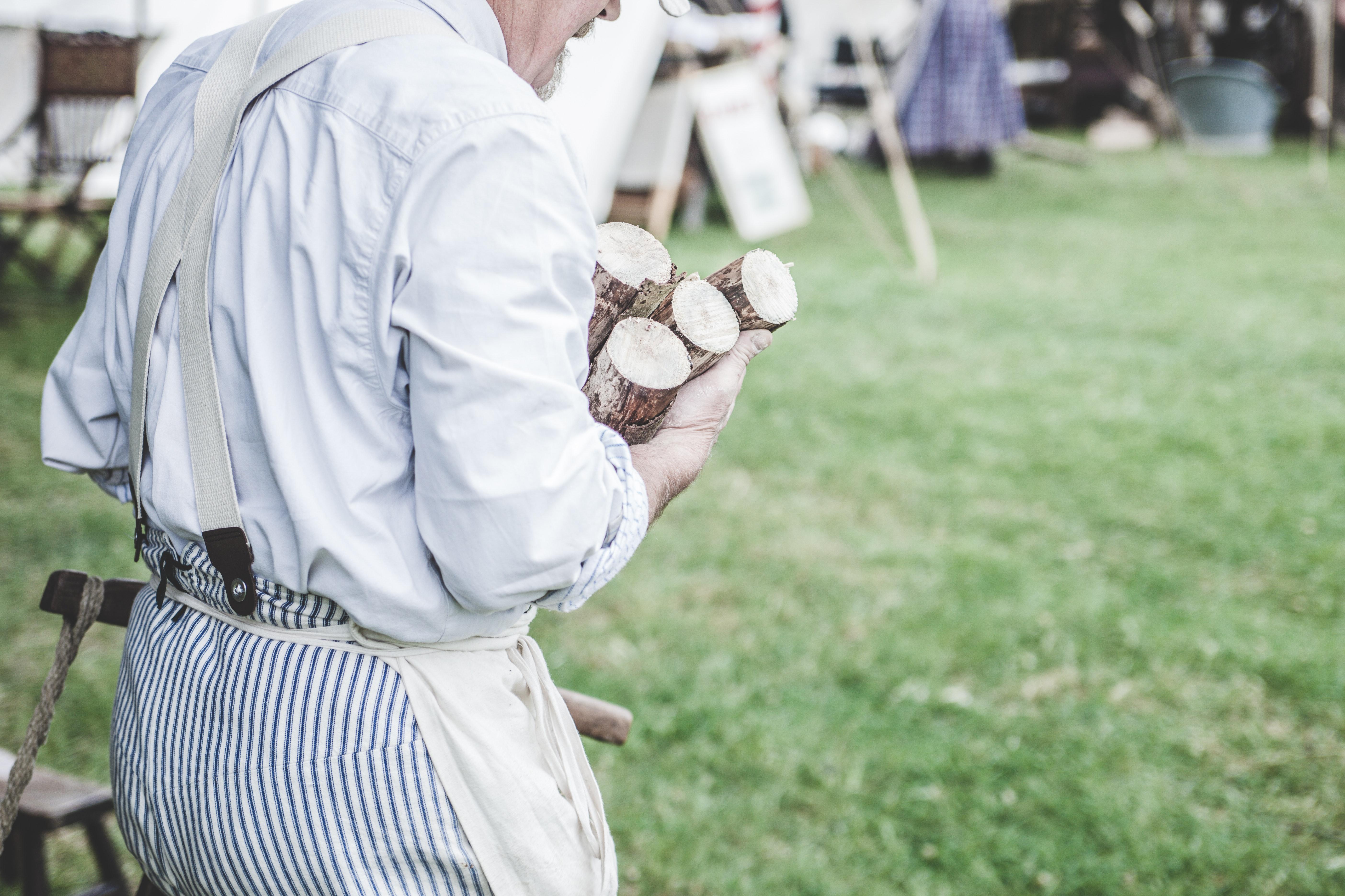 Man in white dress shirt carrying brown wood logs photo
