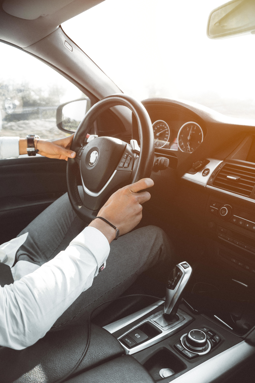 Man in white dress shirt holding steering wheel photo