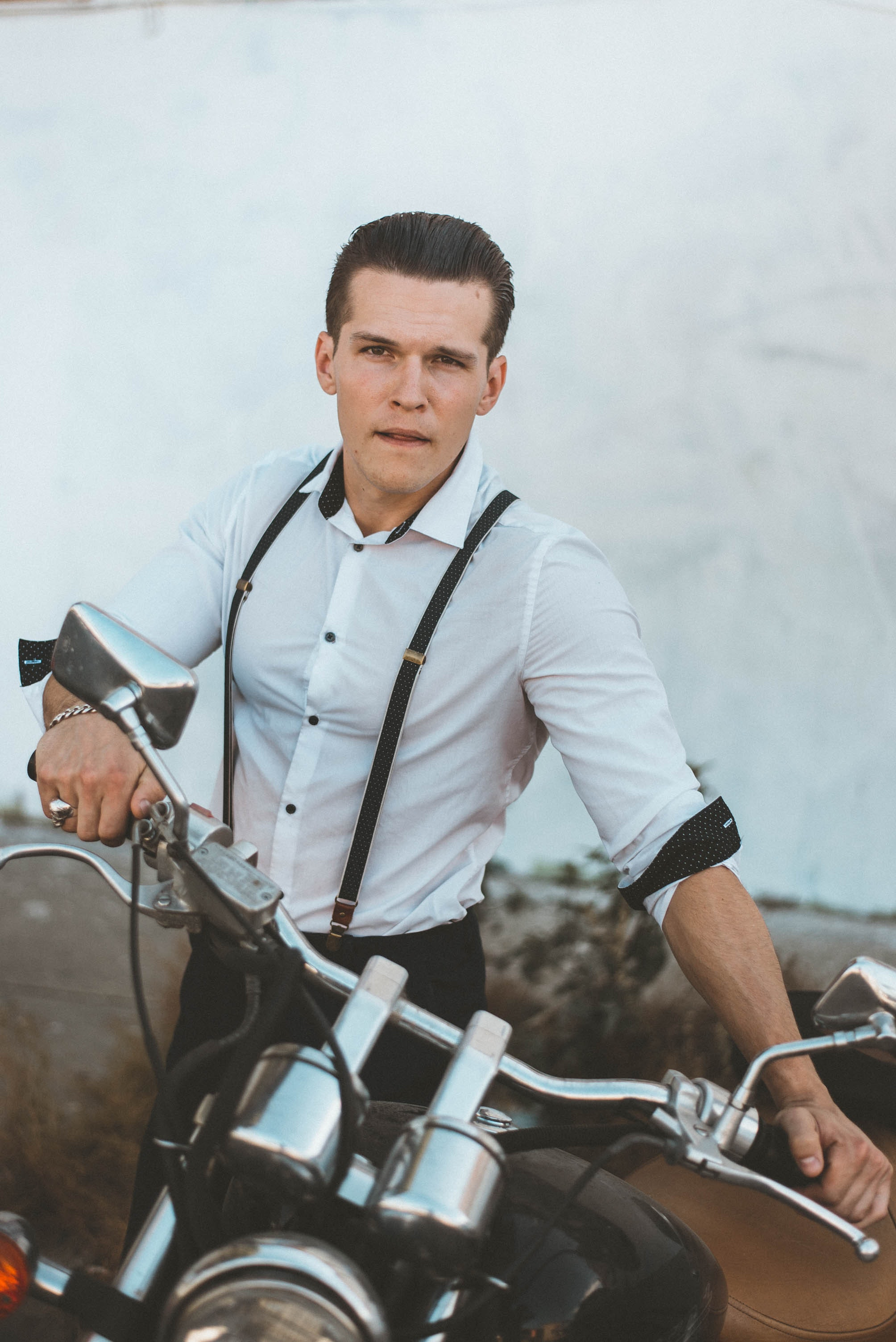Man in white dress shirt with suspenders holding black motorcycle photo