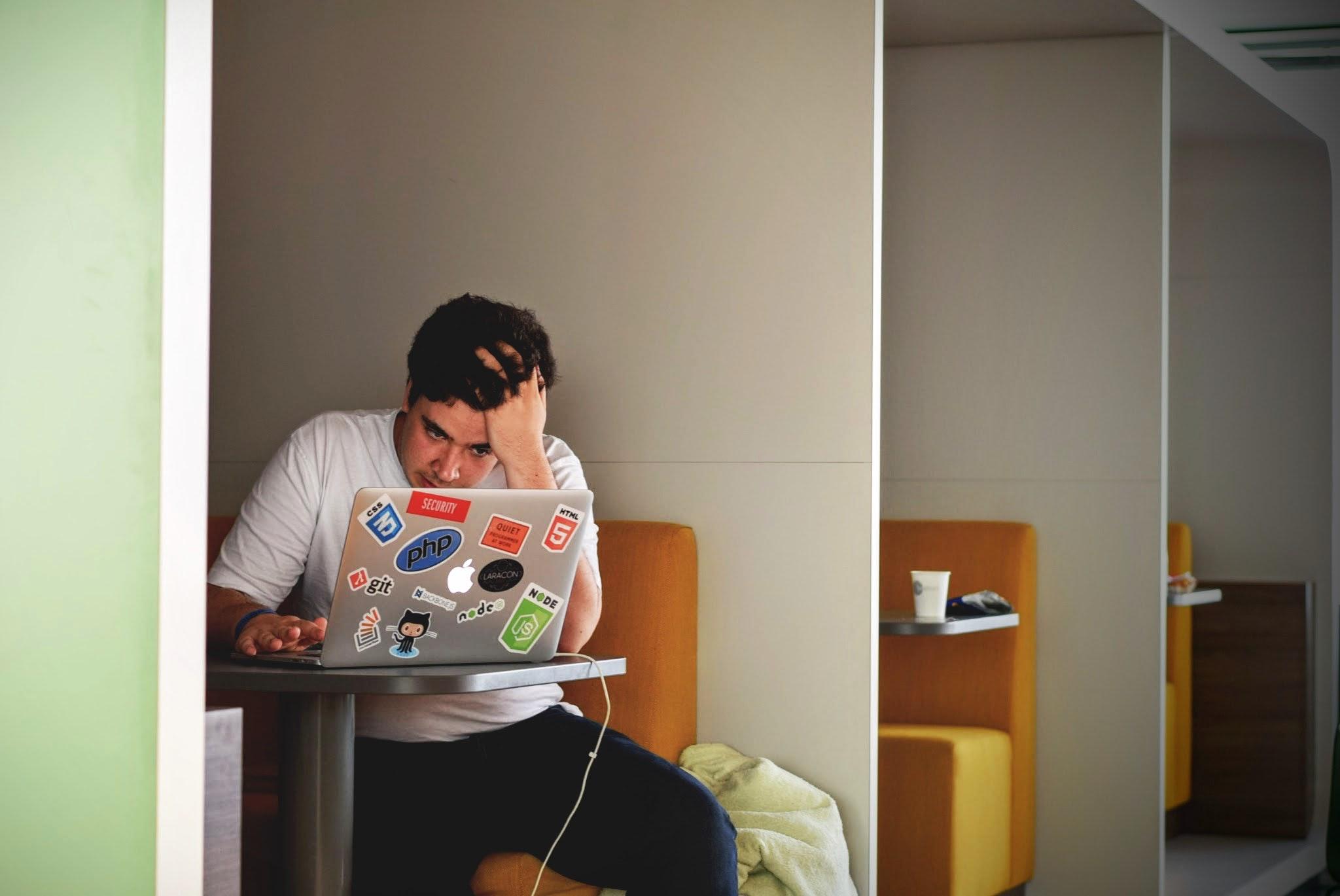 Man in white shirt using macbook pro photo