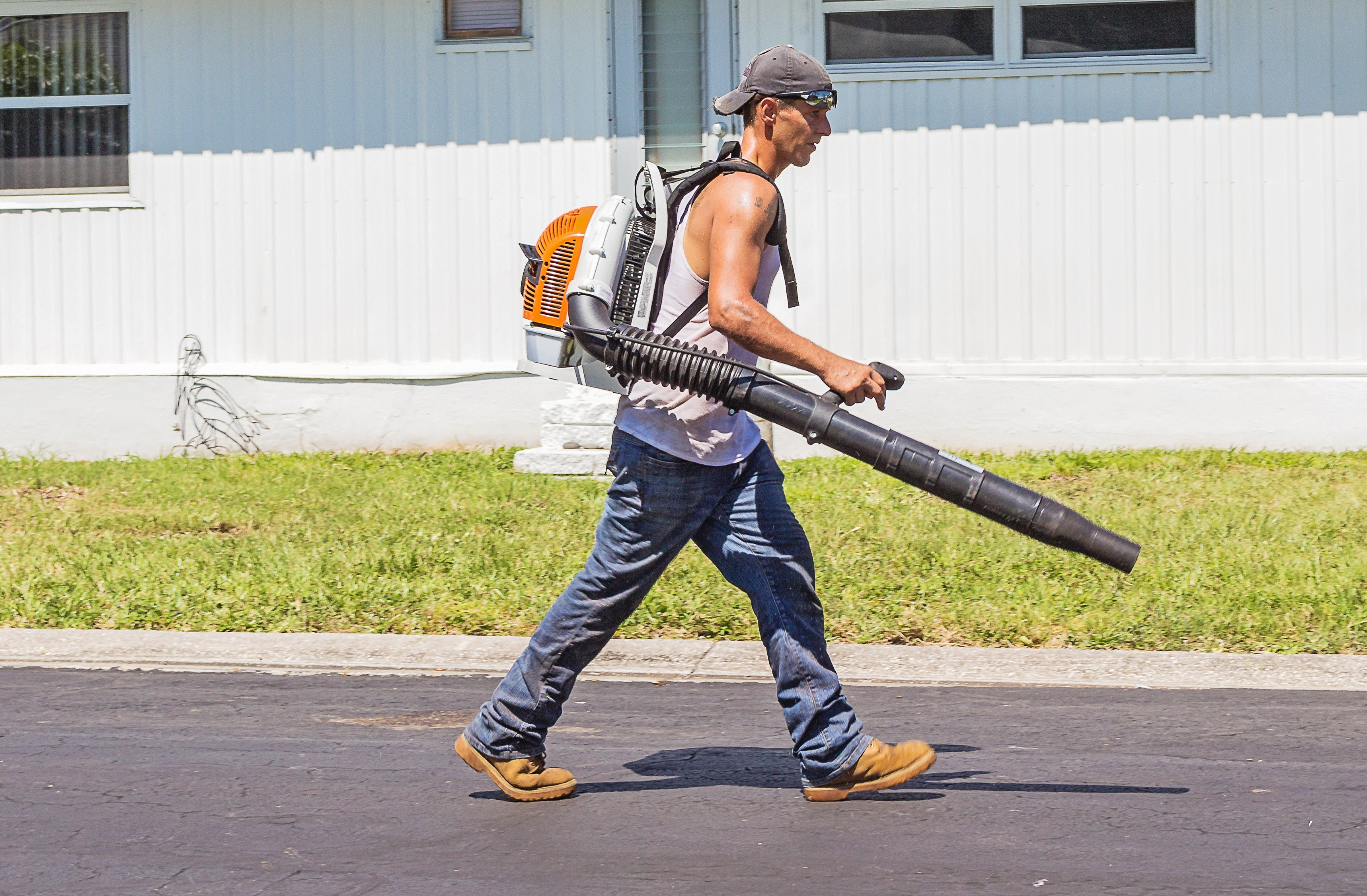 Man in White Tank Top and Blue Denim Pants With Leaf Blower Outdoors during Daytime, Road, Pavement, Shadow, Street, HQ Photo