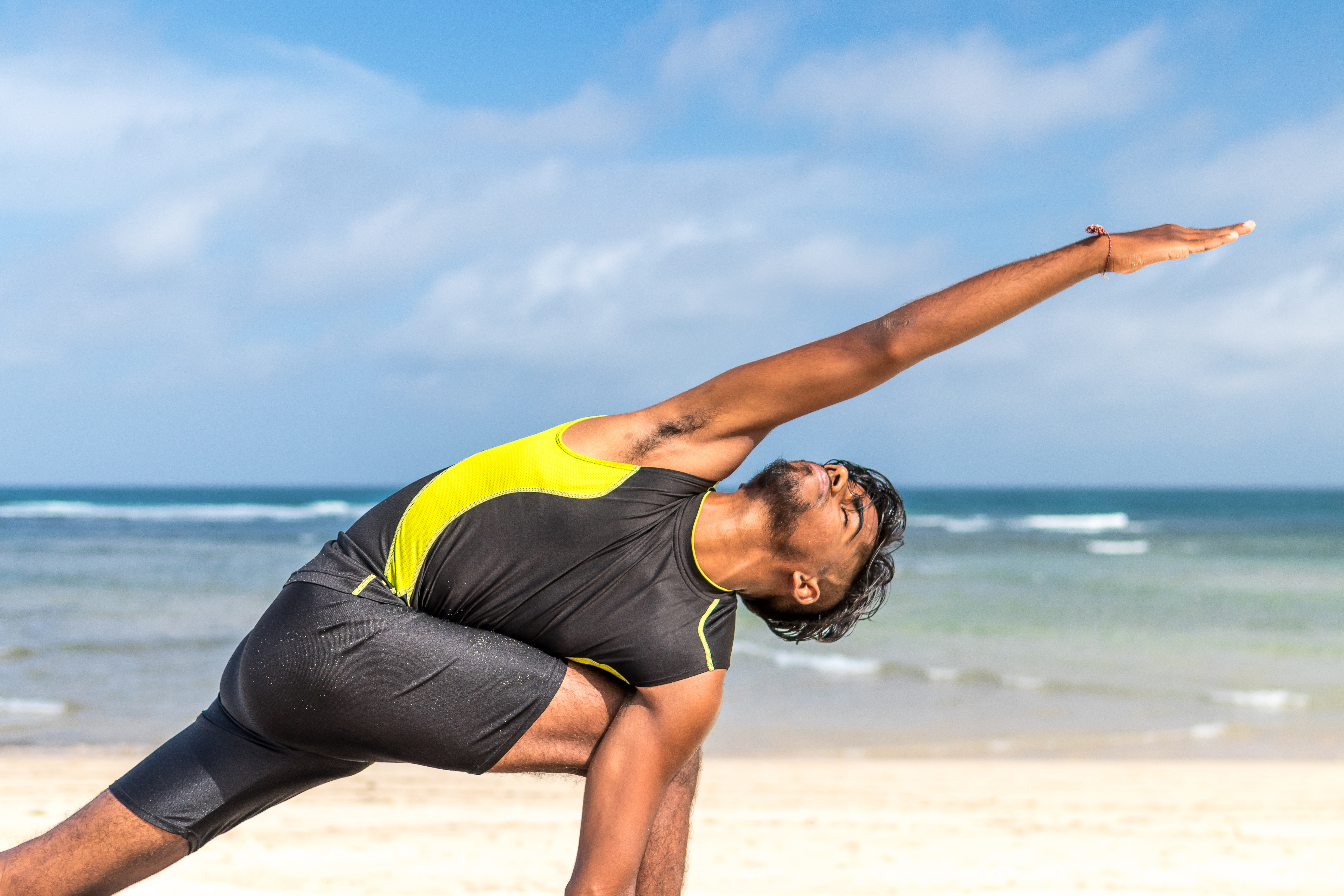 Man in yellow and black tank top doing exercise on seashore at daytime photo