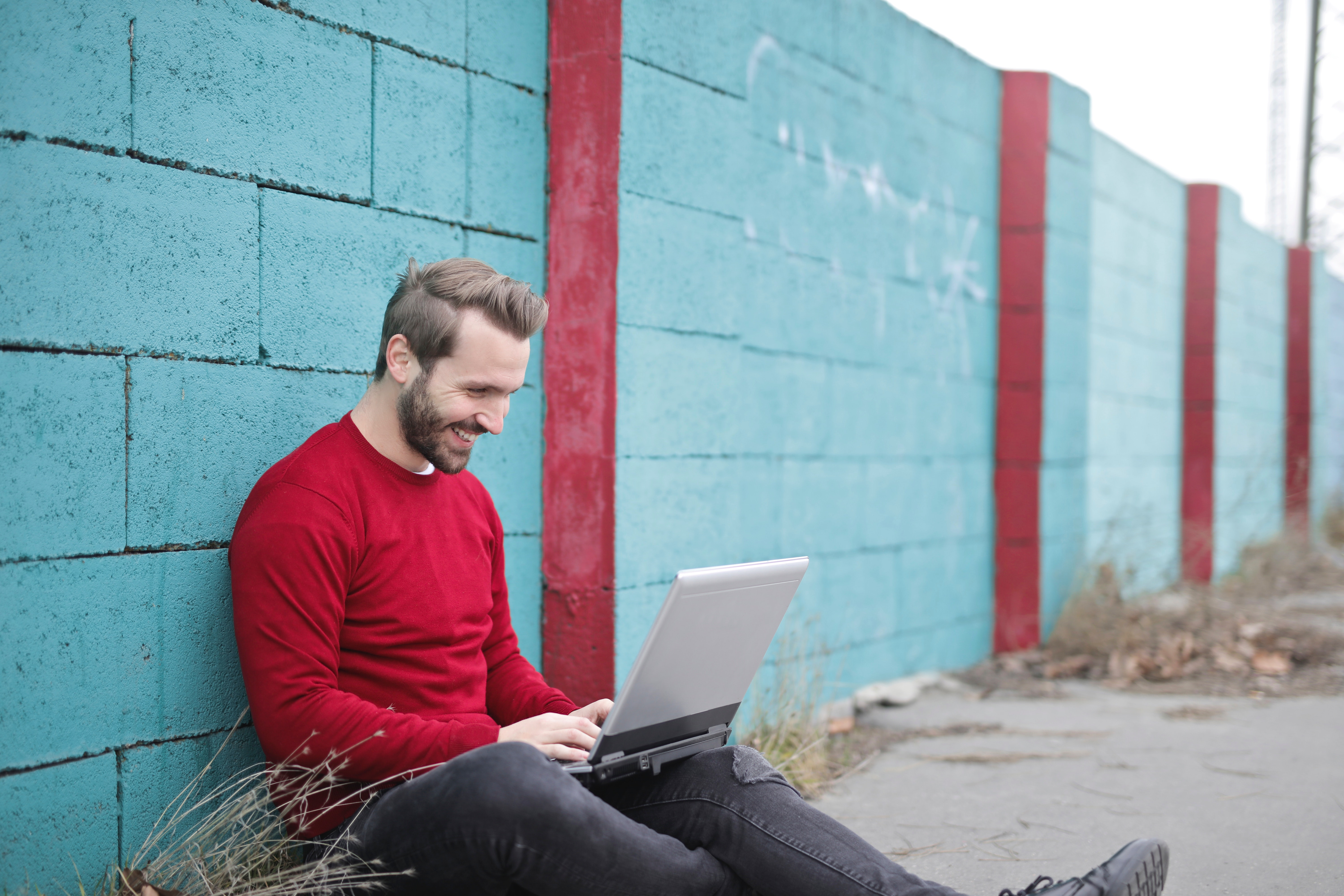 Man leaning against wall using laptop photo