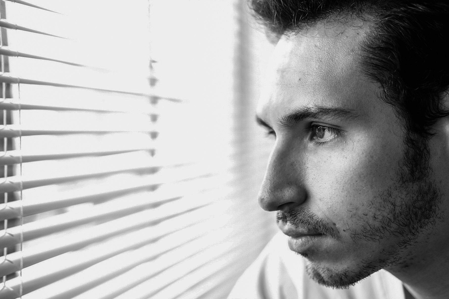 Man looking through window photo