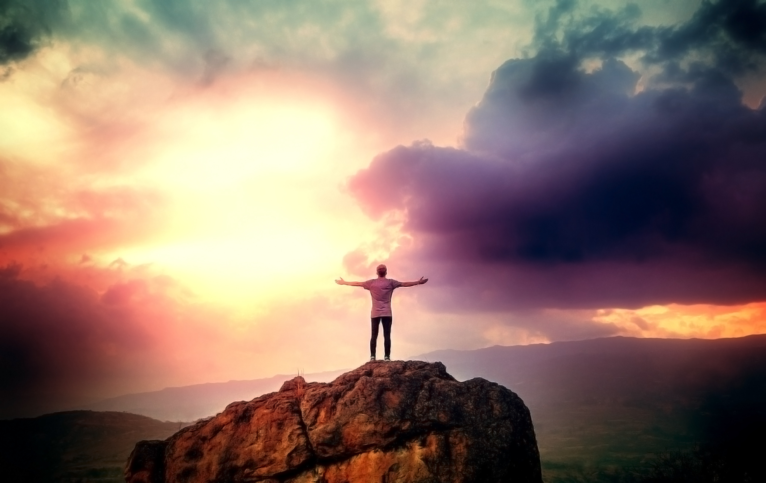 Man on the summit embracing a brave new day photo