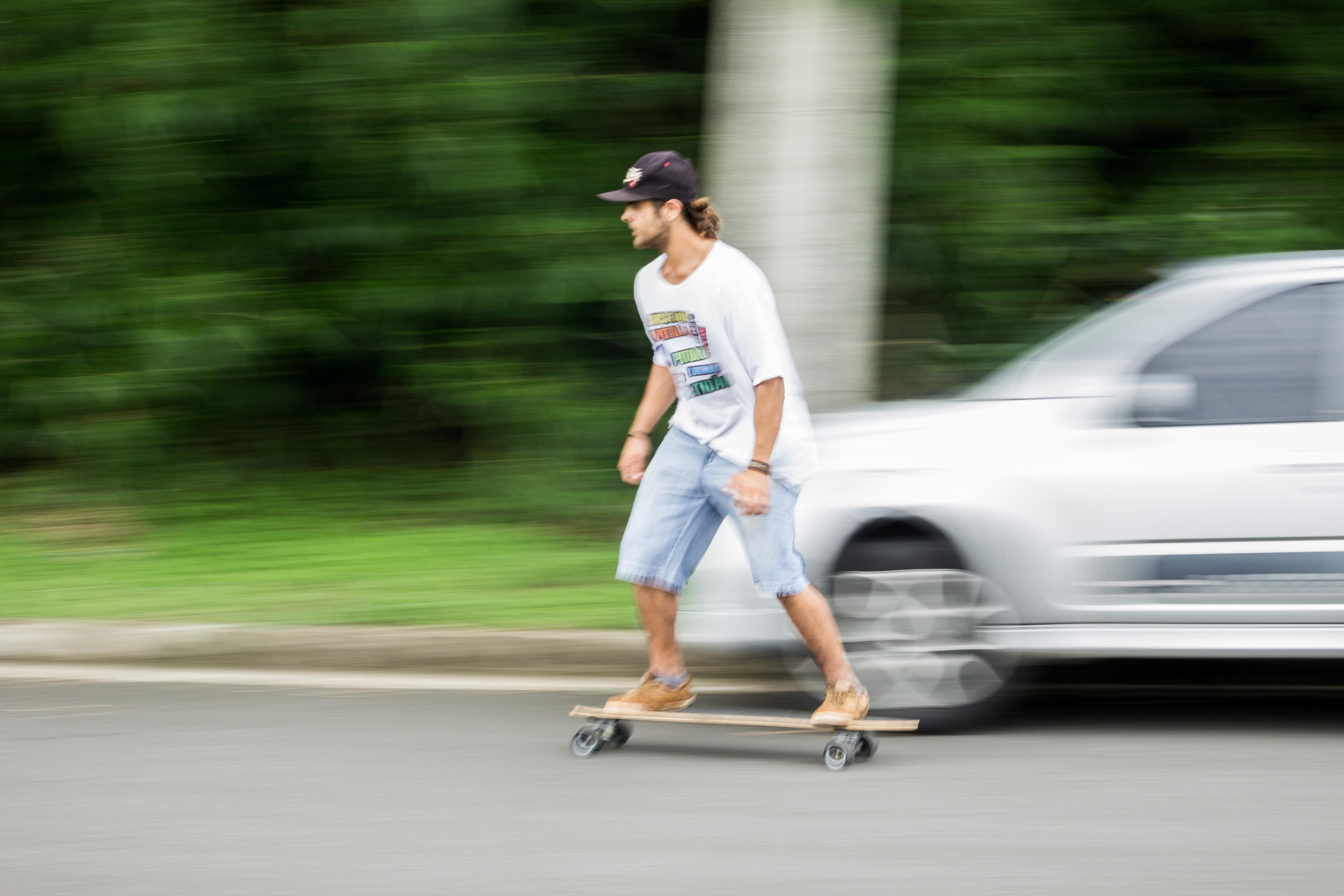 Man playing longboard on road photo