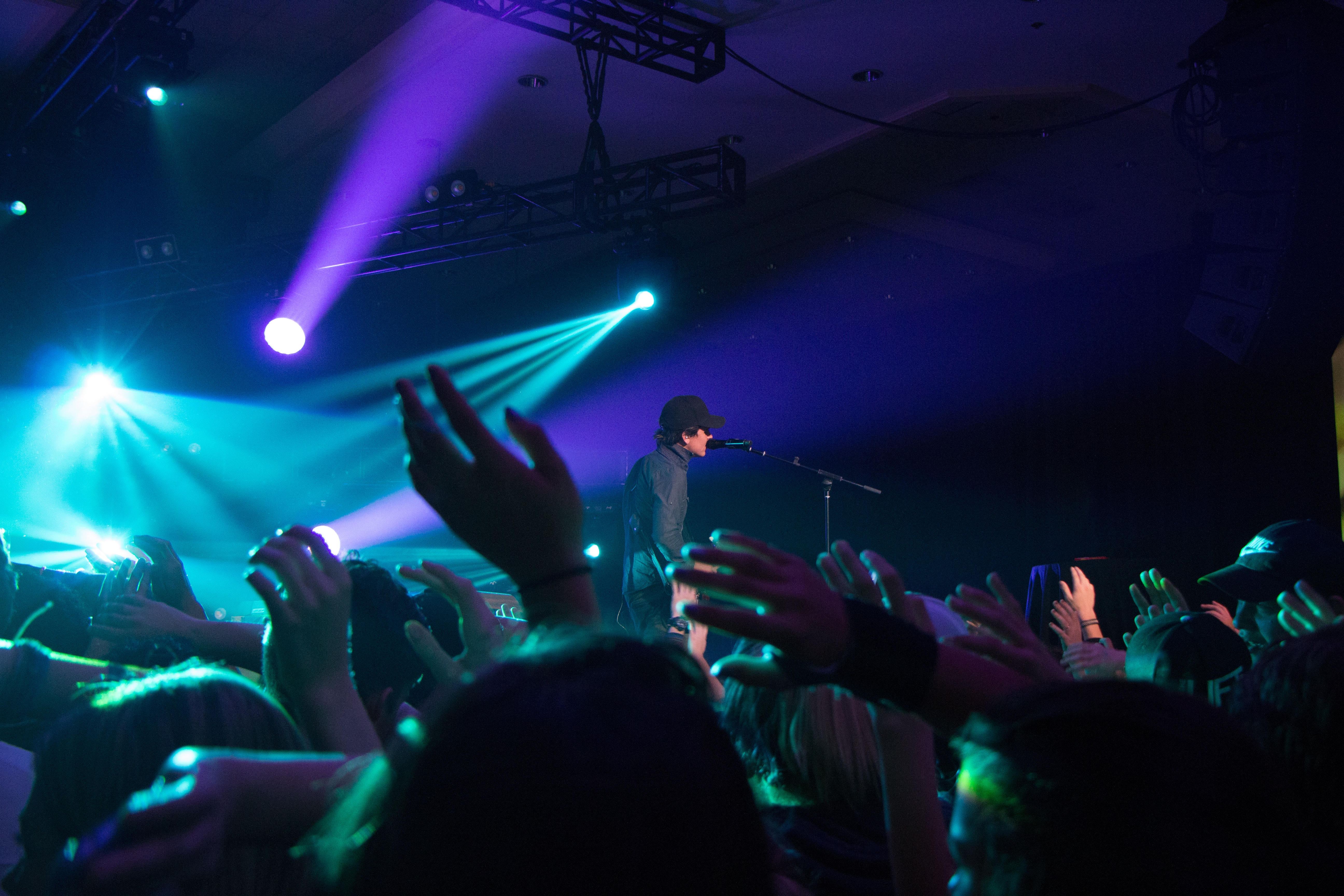 Man singing on stage with stage lights near crowd photo