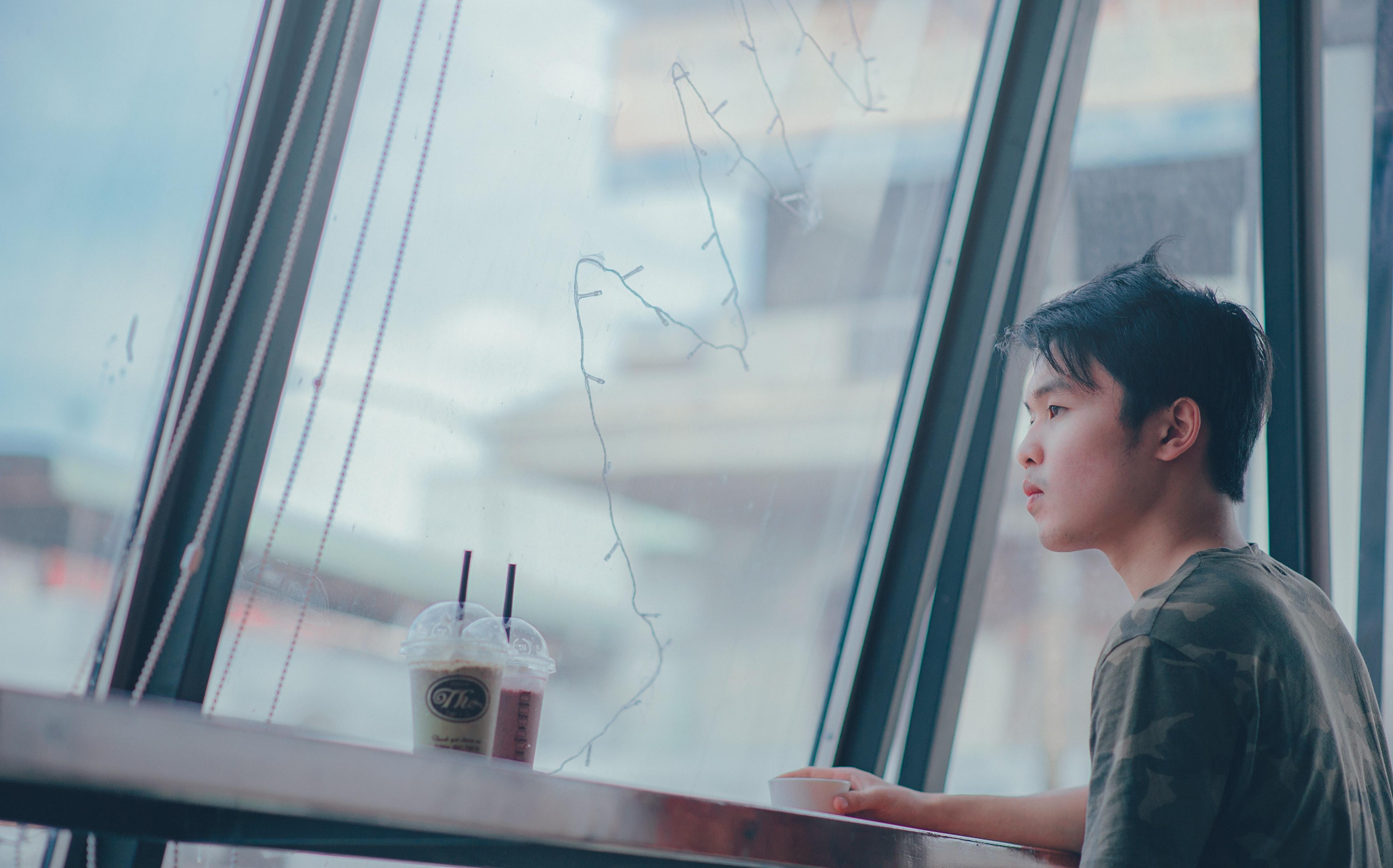 Man sitting beside table near plastic cups photo