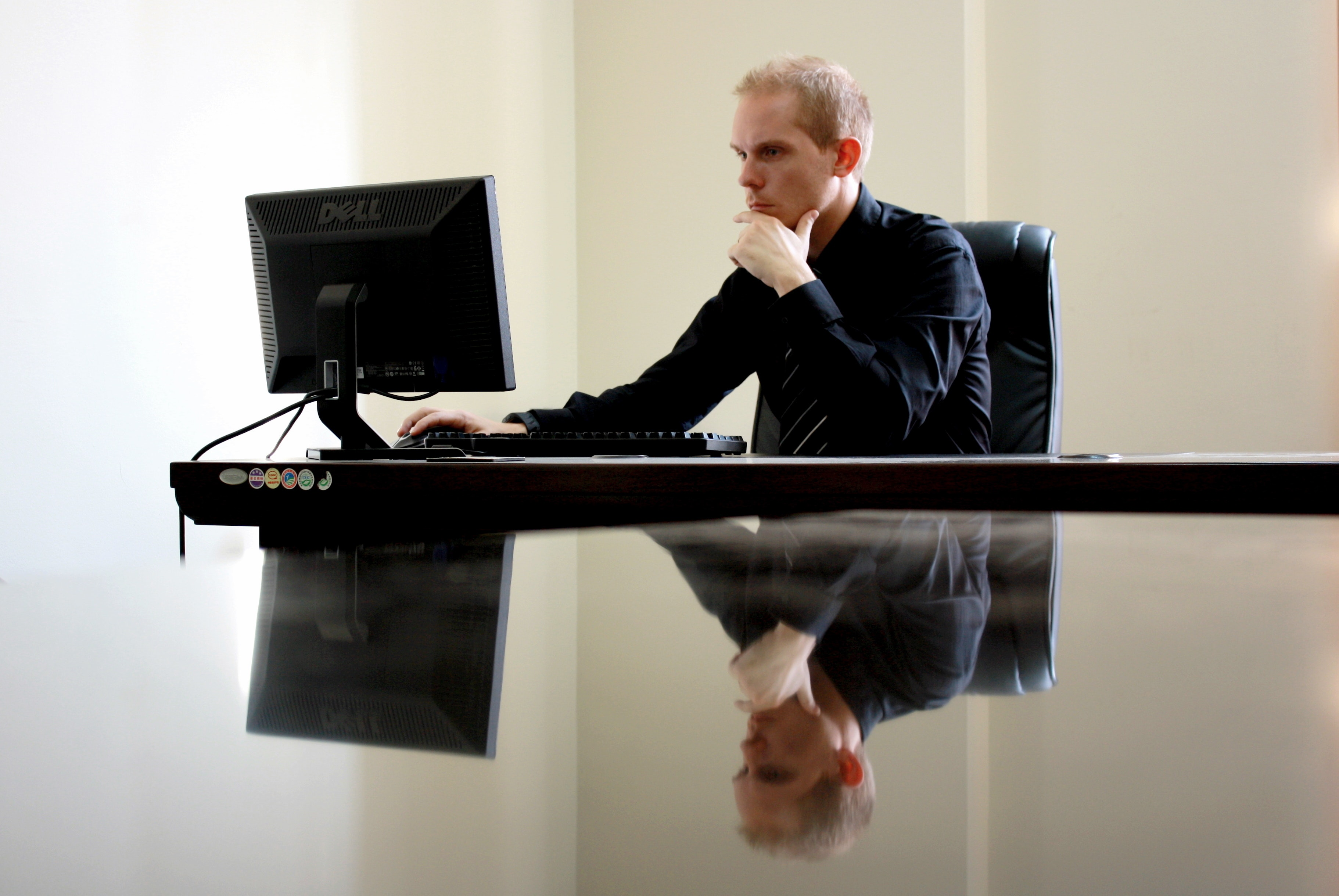 Man sitting facing pc inside room photo