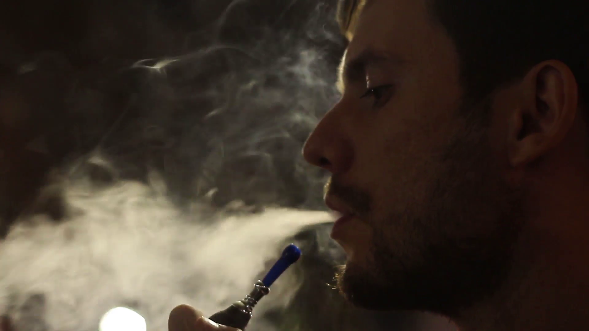 Smoking hookah - a bearded man exhales white smoke backlit . Young ...