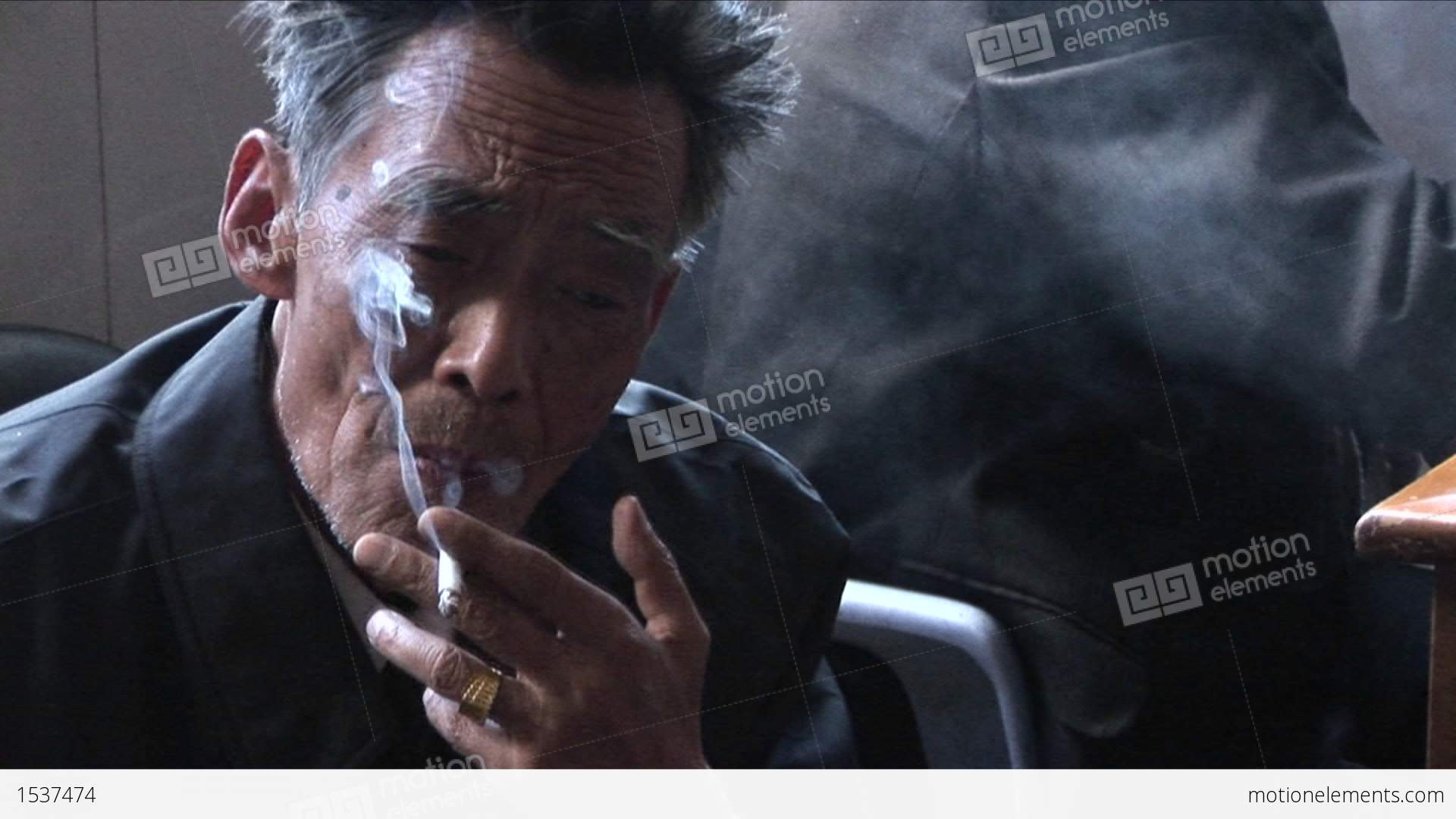 An Old Chinese Man Smokes A Cigarette And Peers At The Camera Stock ...