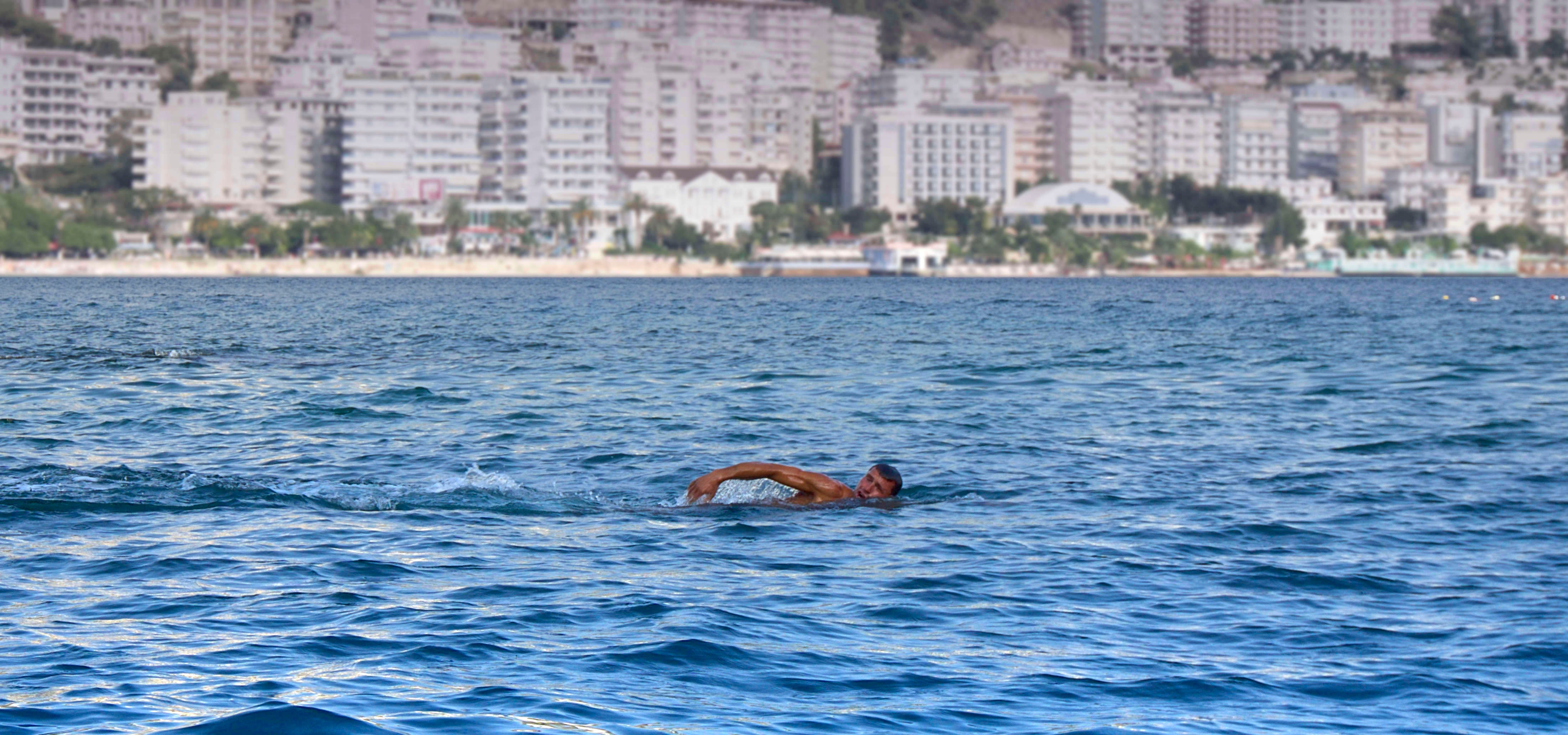 Man swimming in a body of water white concrete high rise building in background photo