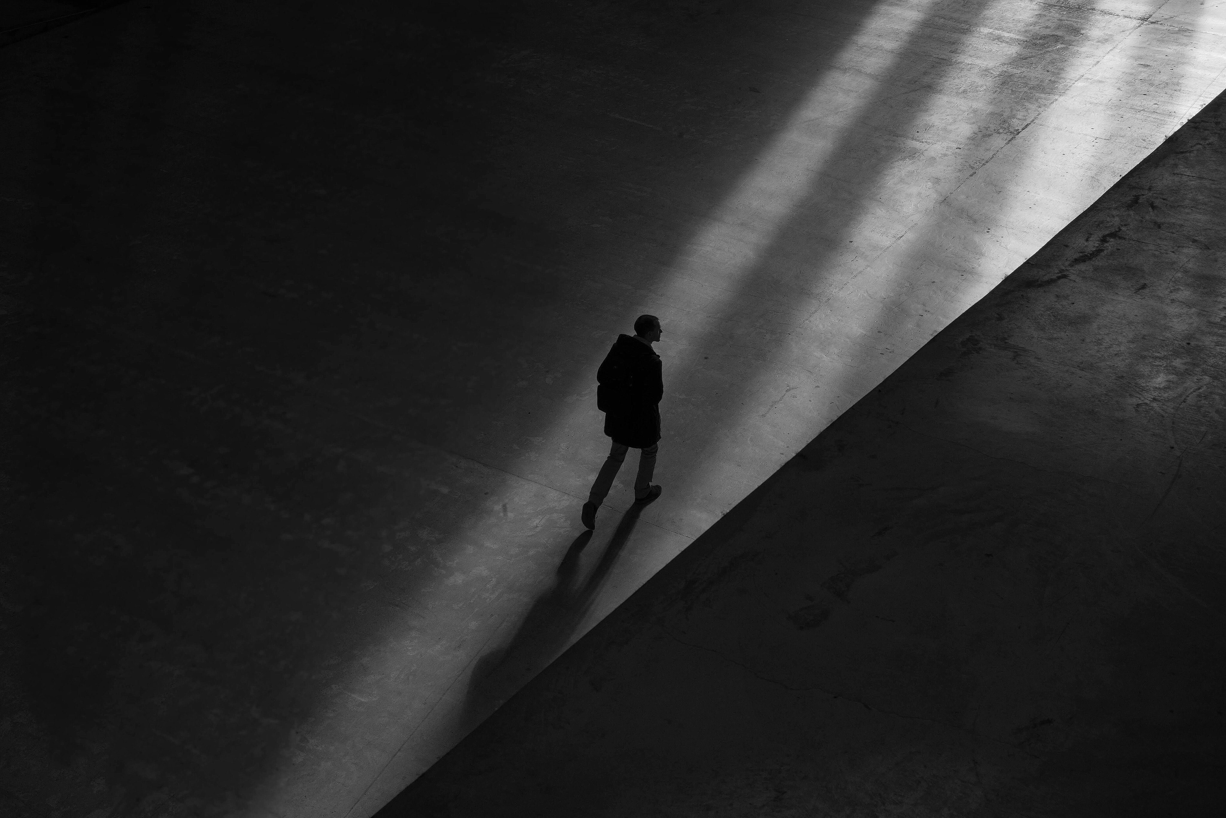 Free photo man walking on floor alone black and white